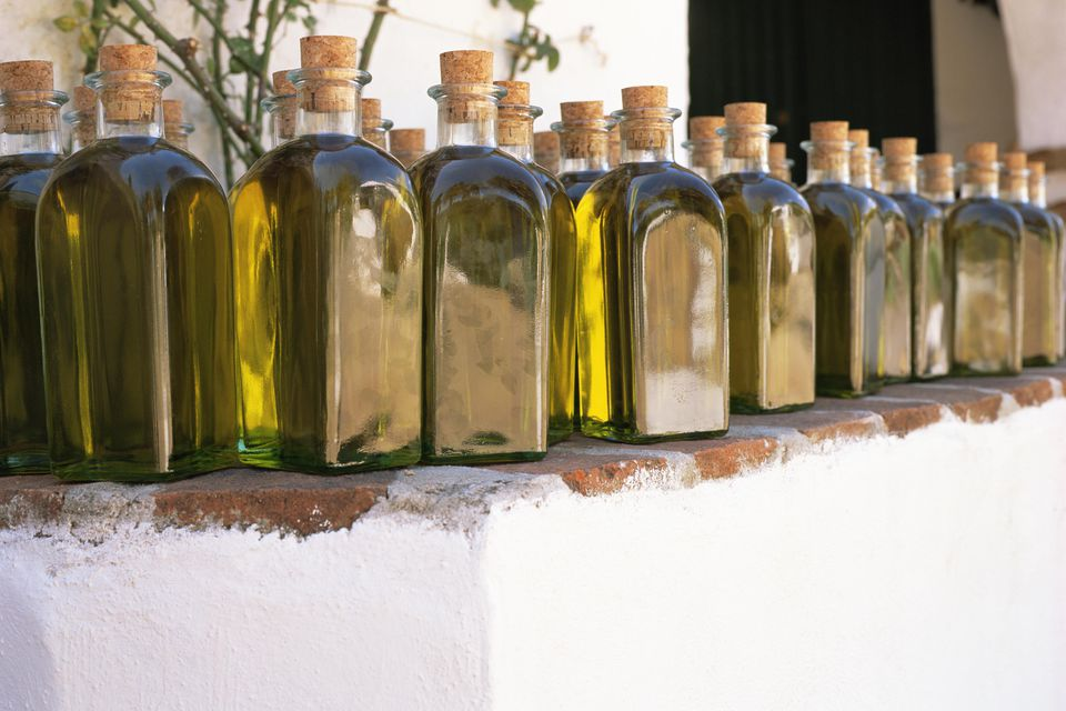 Many jars of olive oil on an outdoor ledge