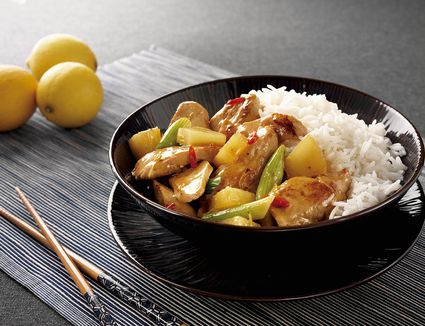 Sweet and sour chicken with pineapple and rice in a bowl with chopsticks