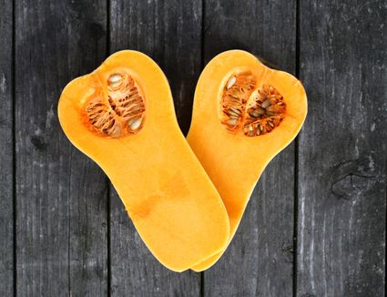 Two halfs of a butternut squash on an old wooden garden table