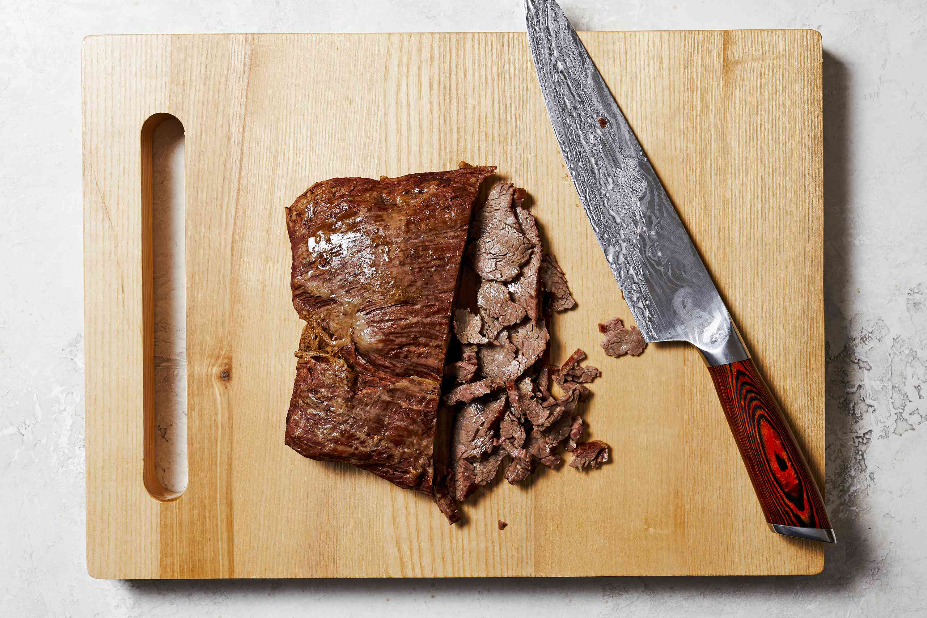 A photo of flank steak on a cutting board with slices cut