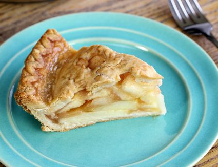 apple pie on a green plate on a wooden table