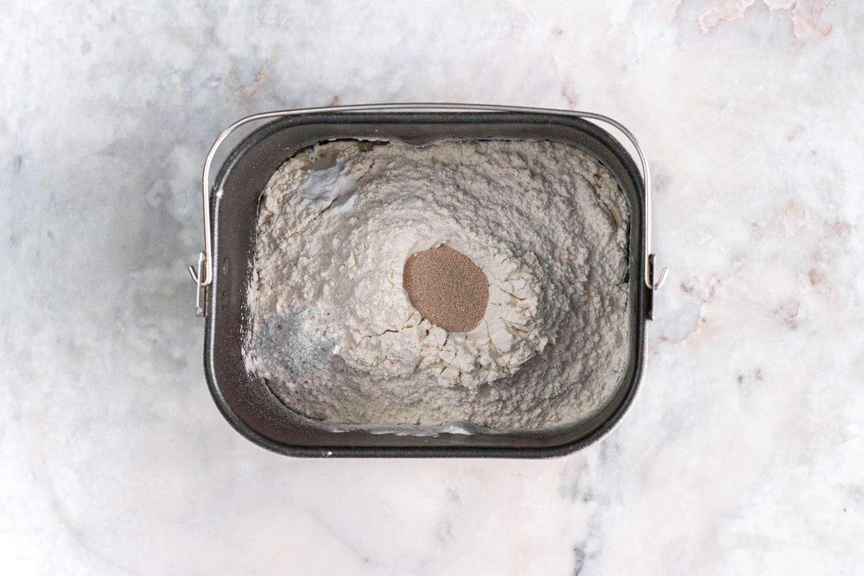 Flour, yeast, baking soda, salt, water mixture in a bread machine basket