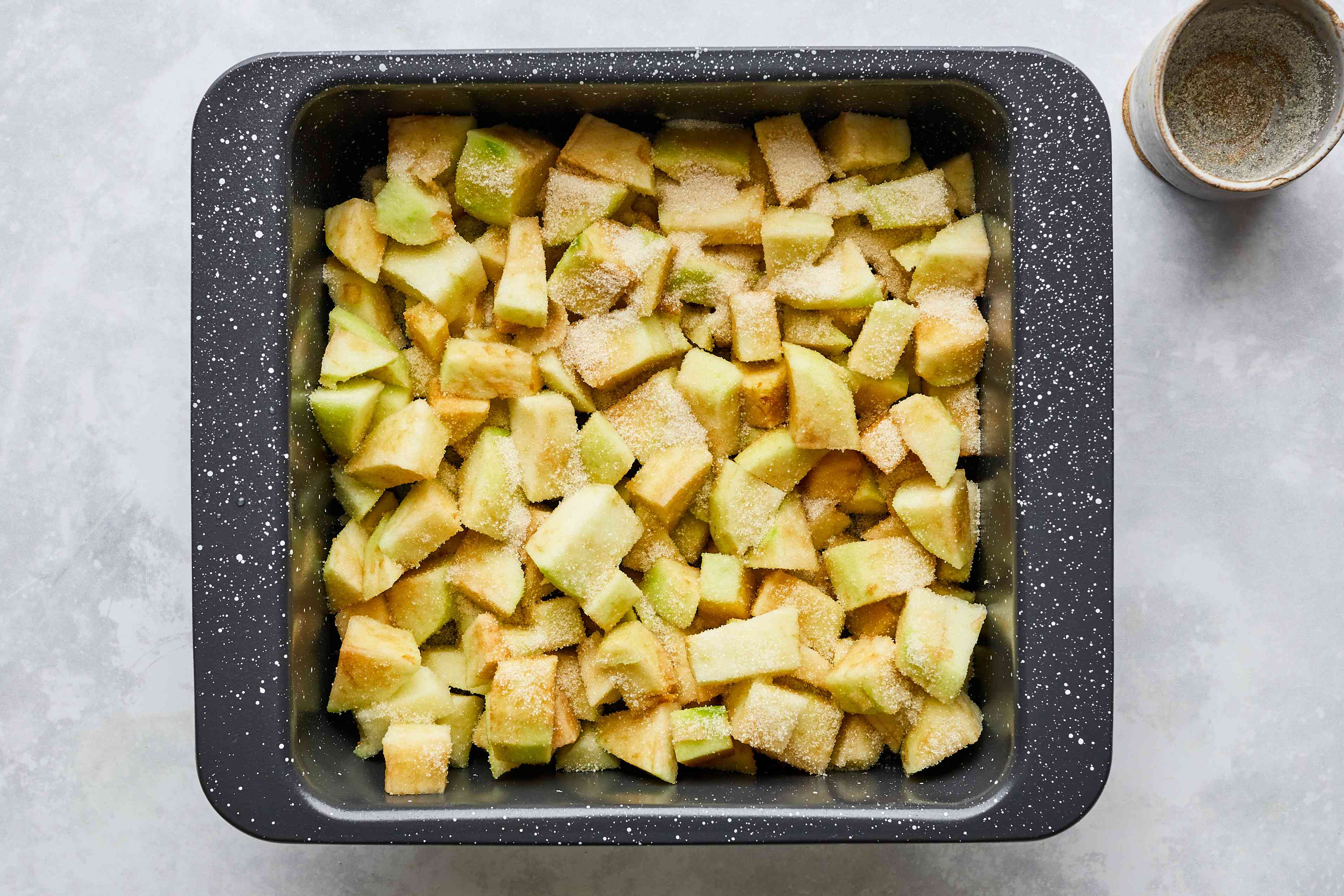 Diced apples and sugar in a shallow baking dish