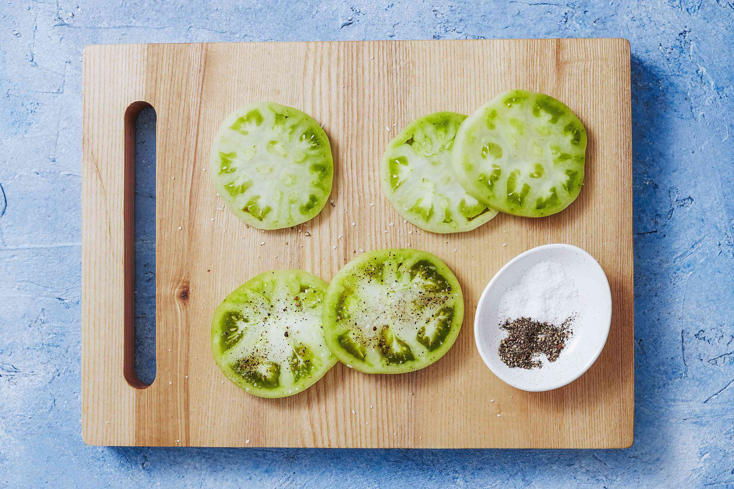 A cutting board with slices of green tomatoes with salt and pepper