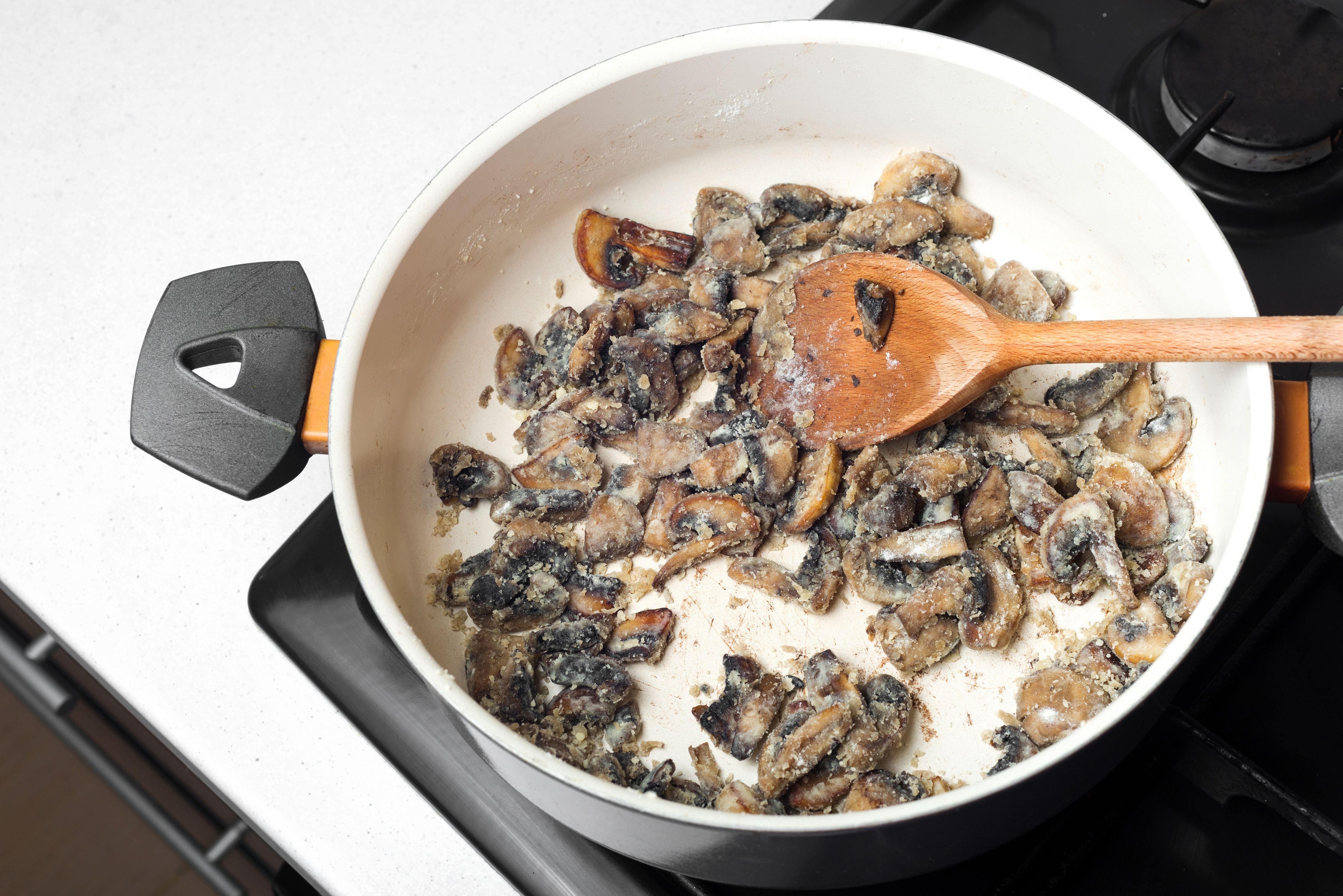 Stir in flour to mushrooms in saucepan