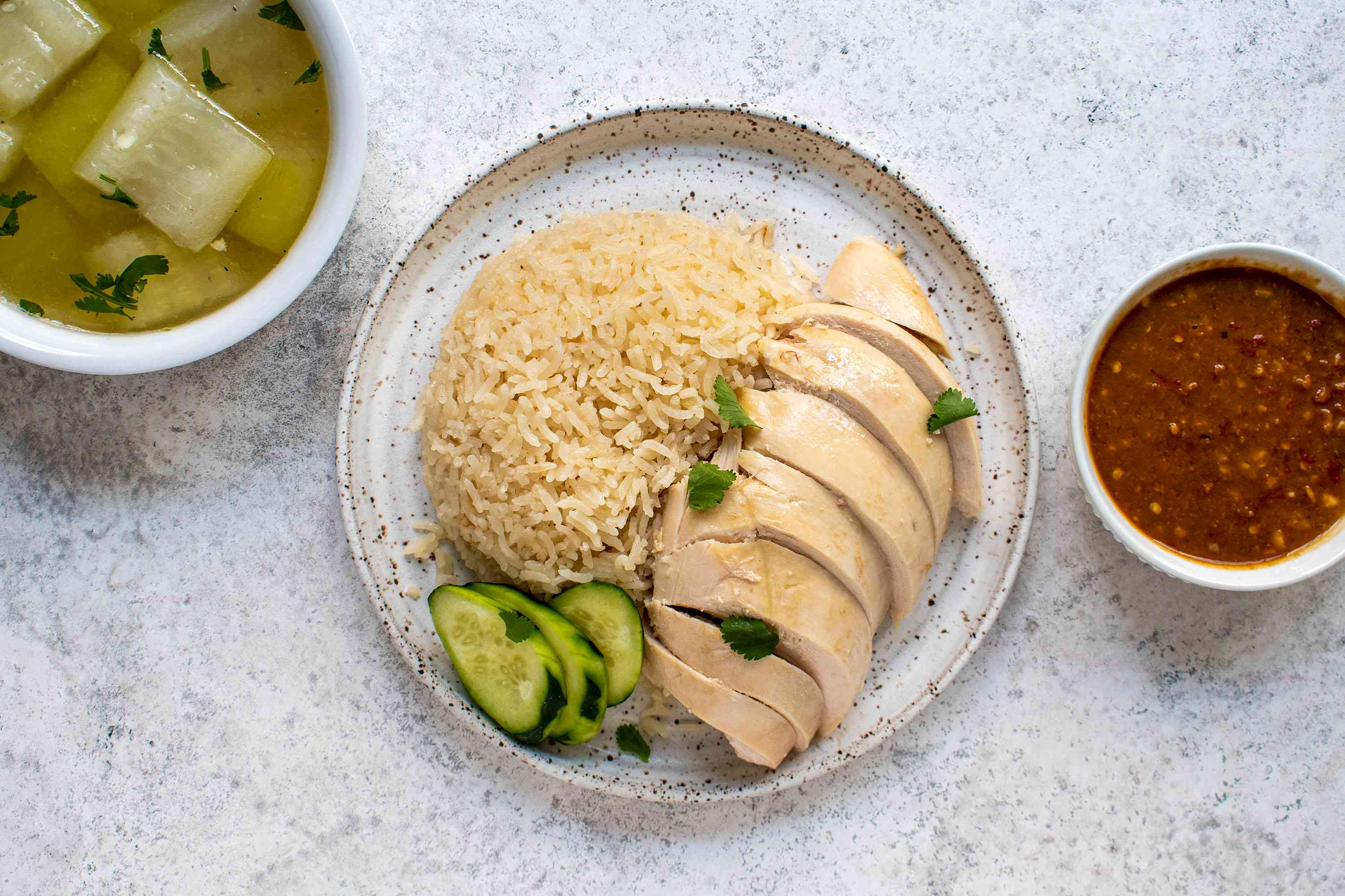 Thai Khao Man Gai, Place the sliced breast meat on top of the rice mound, garnishing it with sliced cucumber and cilantro