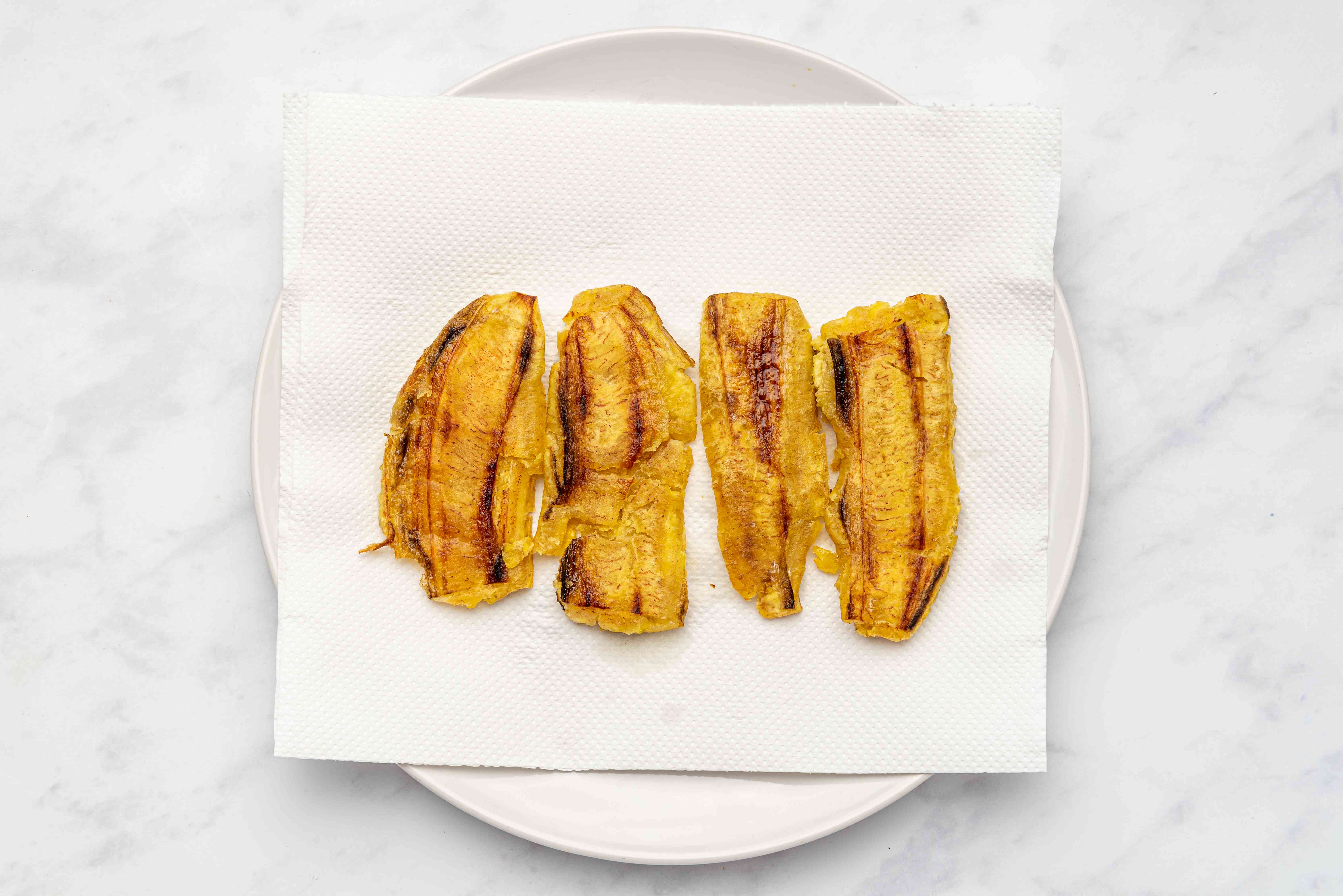 Flatten the plantains and continue to cook in a pan