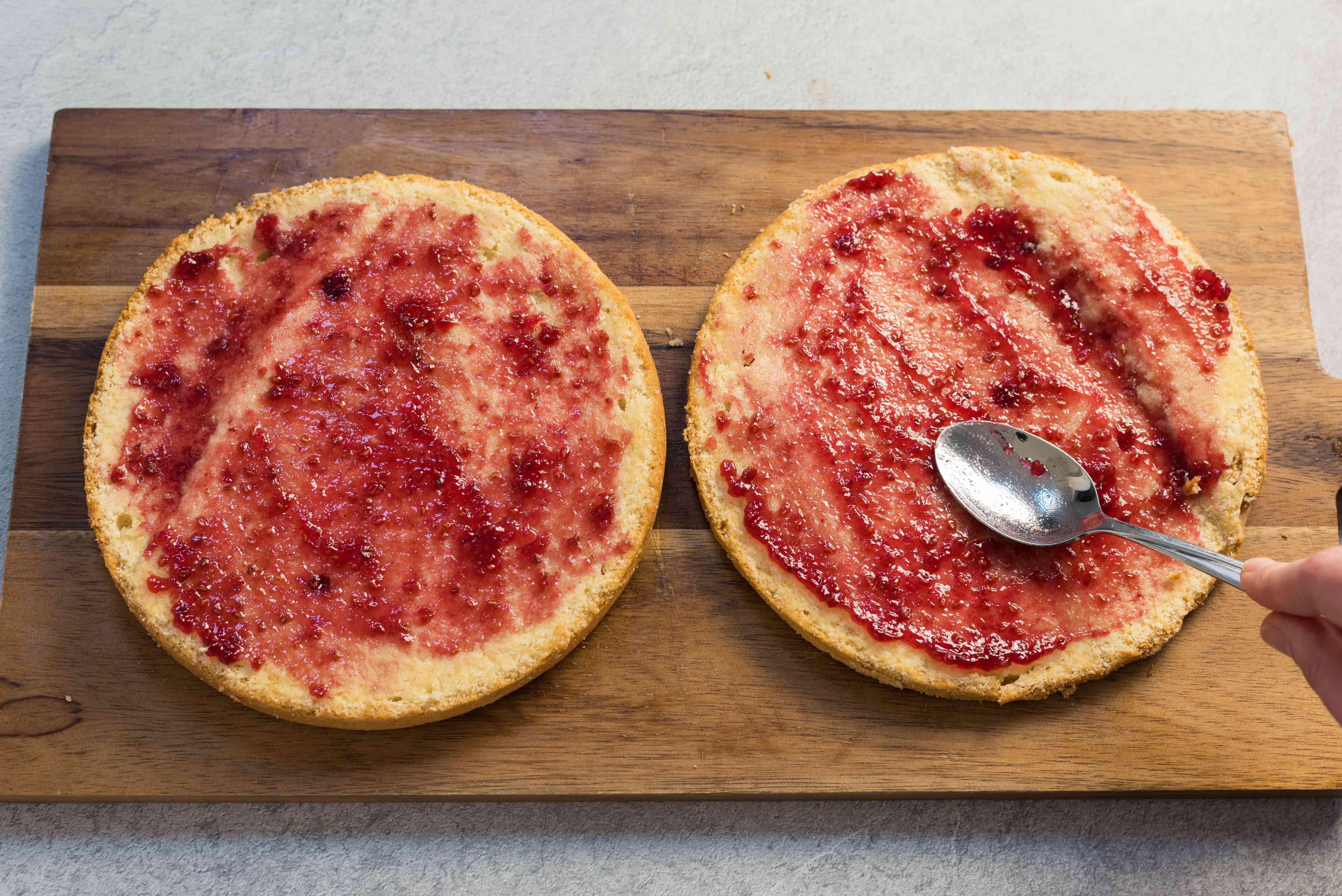 Spread raspberry jam onto cake