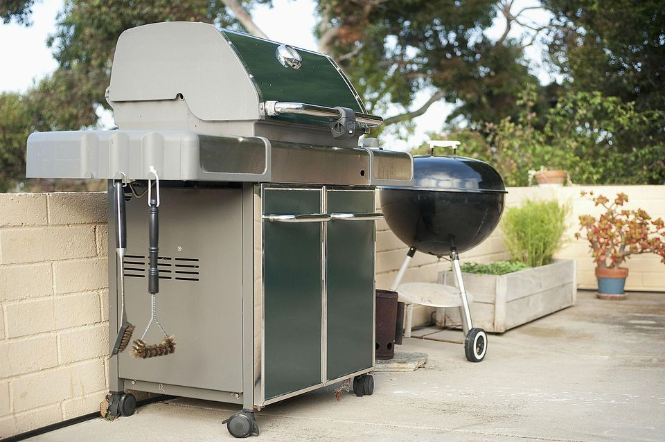 Gas grill and barbecue grill in yard