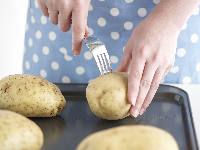 pricking baking potato with fork