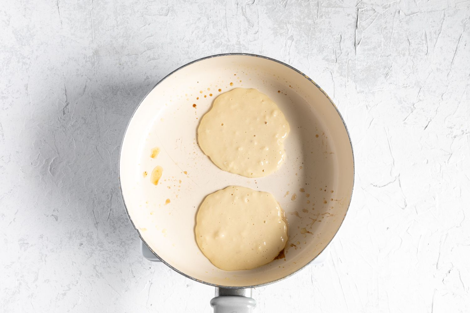 Pancakes cooking in a greased skillet