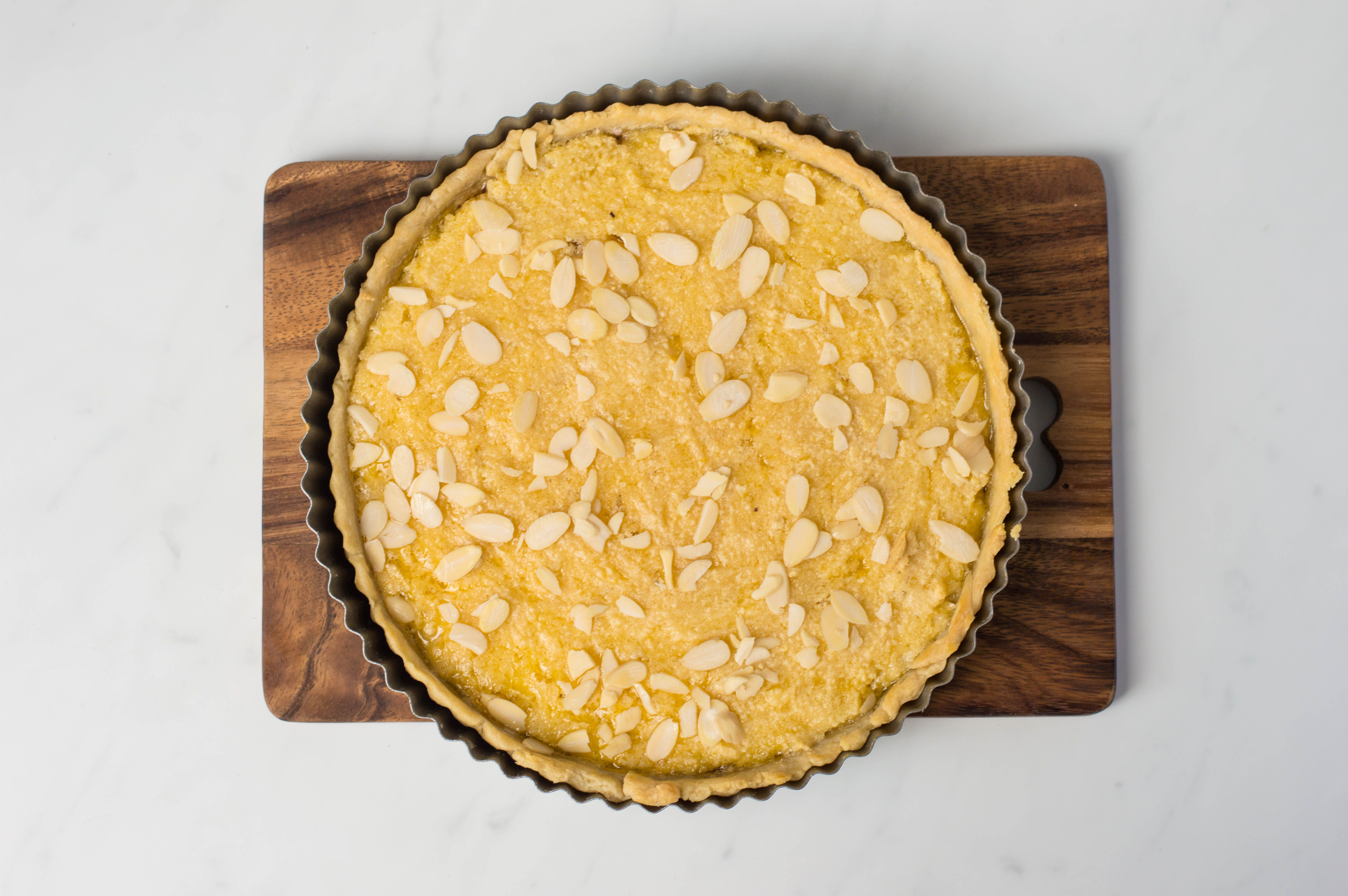 Tart sprinkled with flaked almonds on wooden board