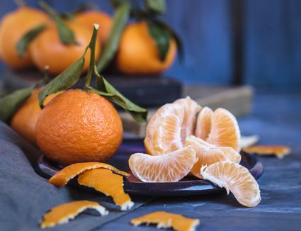 Small oranges, whole with stems and one peeled and segmented