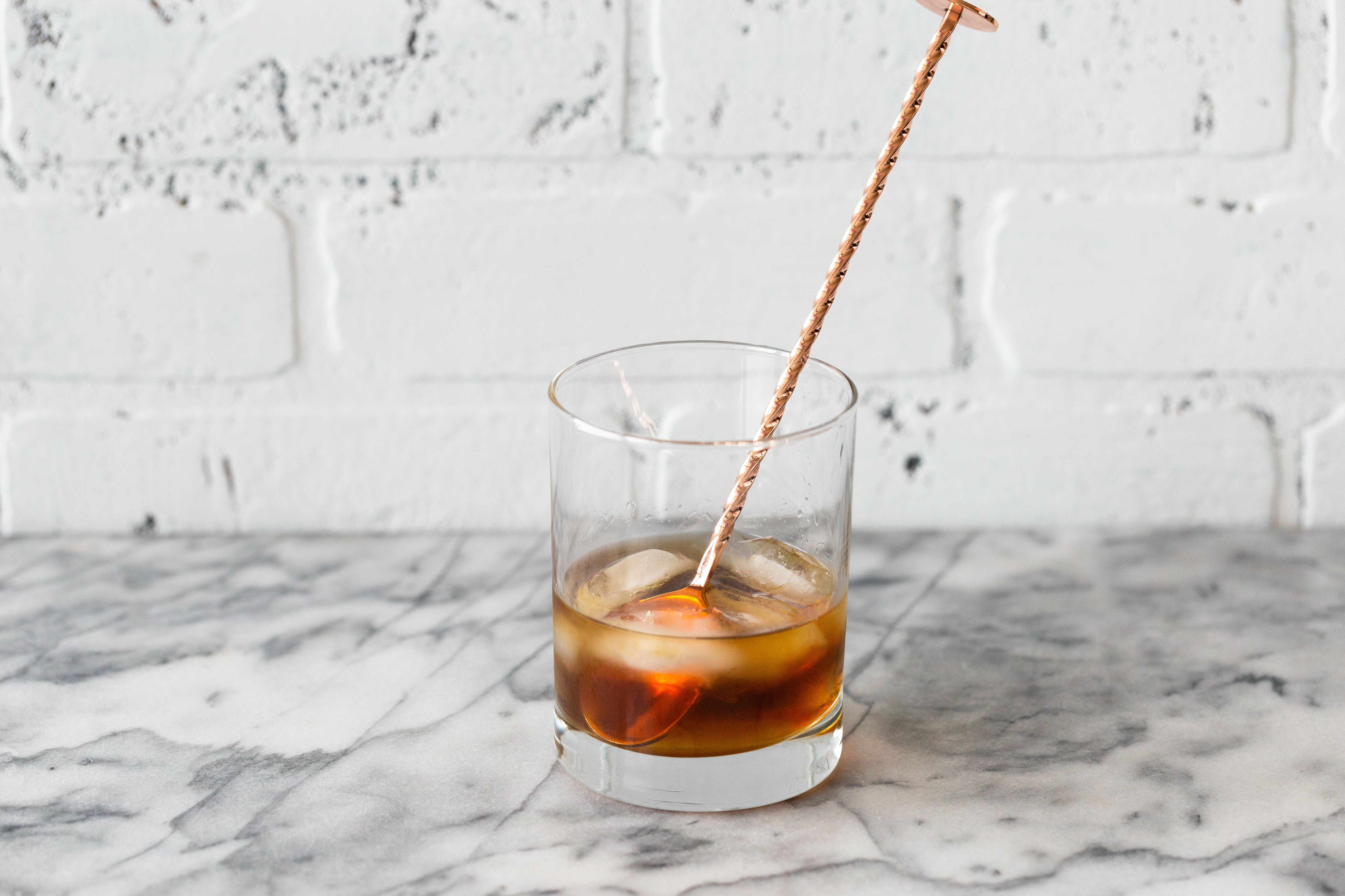 Black Russian cocktail with a stirrer.