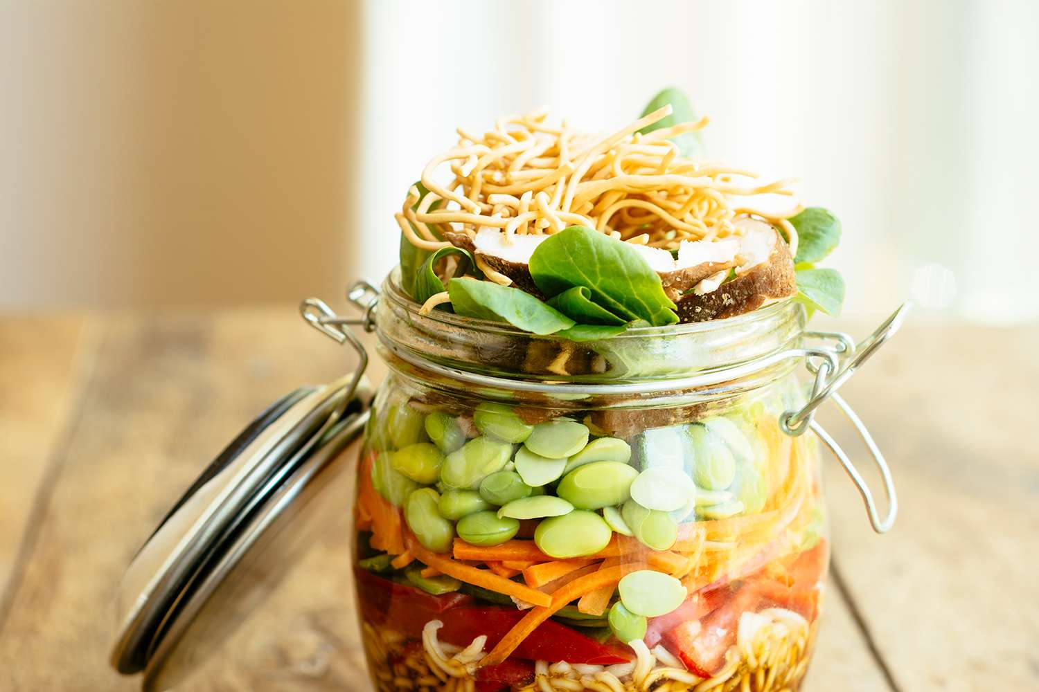 Asian salad in a jar with ramen noodles, red pepper, snow pea pods, carrots, edamame, shiitake mushrooms, salad greens, fried chow mien noodles and dressing
