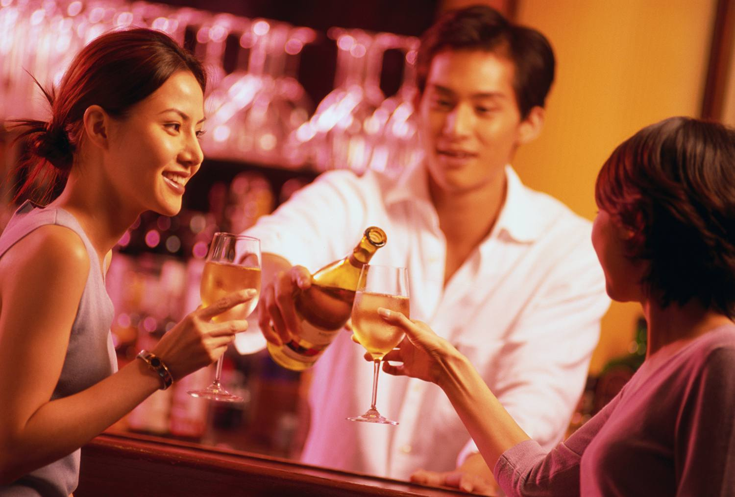 A bartender pouring two women wine