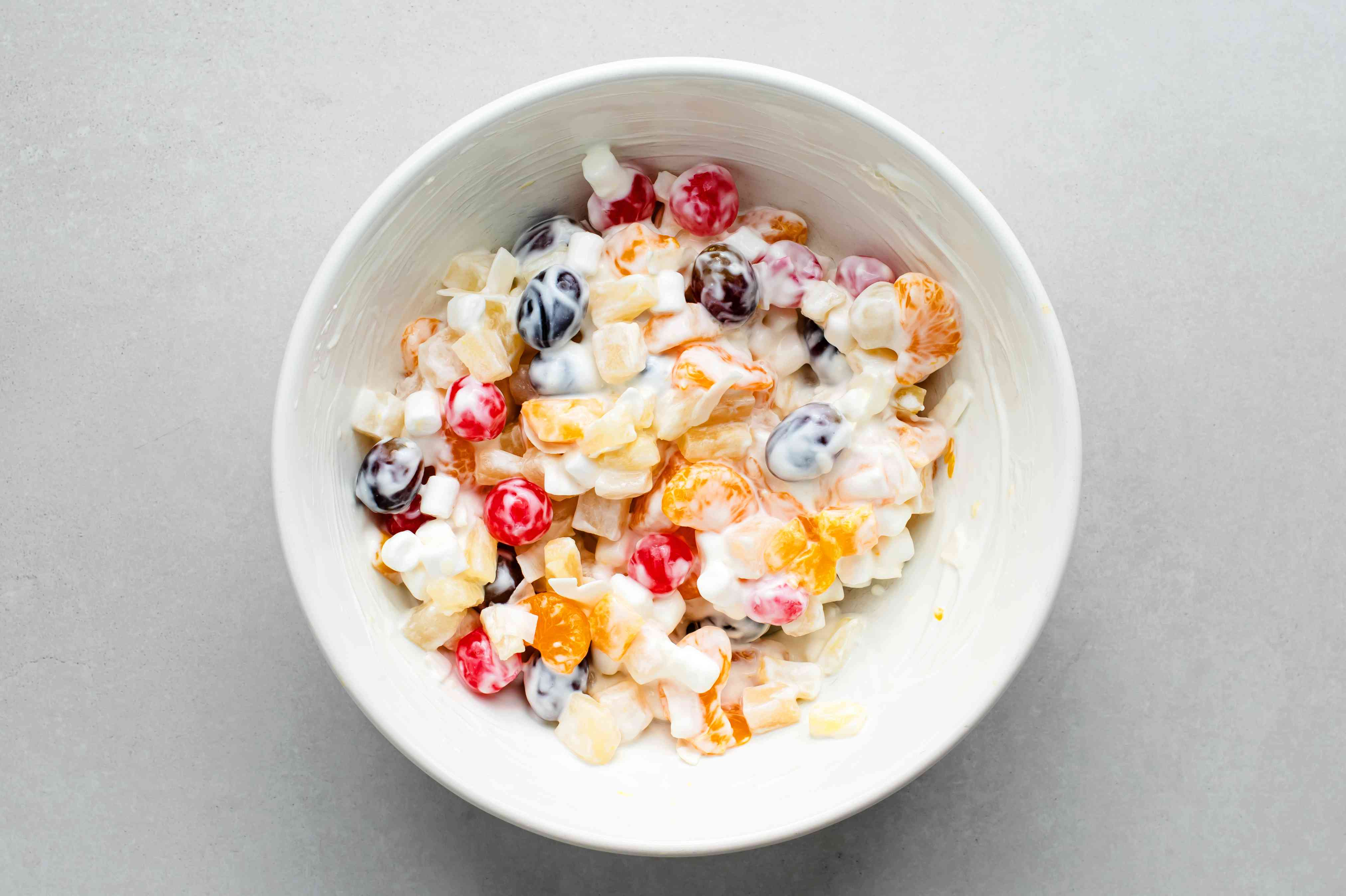 rained fruits, marshmallows, sour cream, and coconut in a bowl