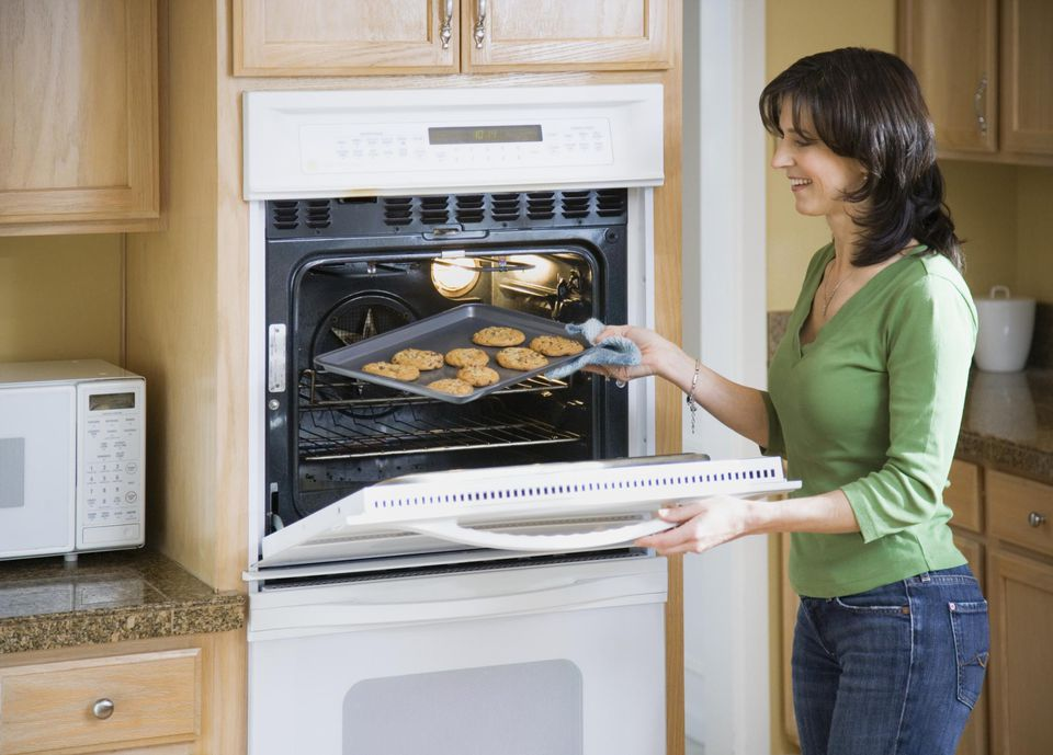 Mature woman taking baking sheet and cookies out of oven, smiling