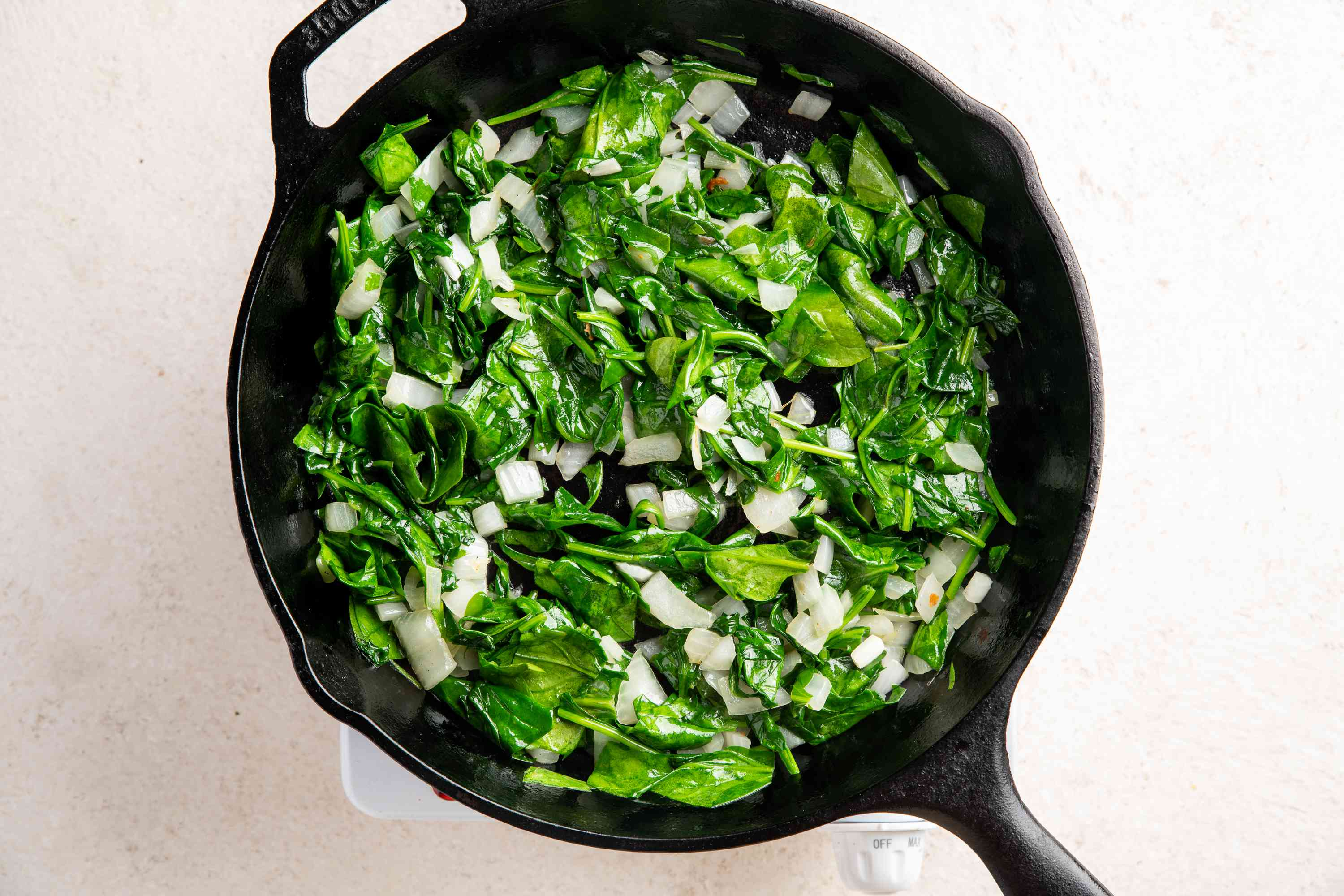 spinach and onions cooking in a pan