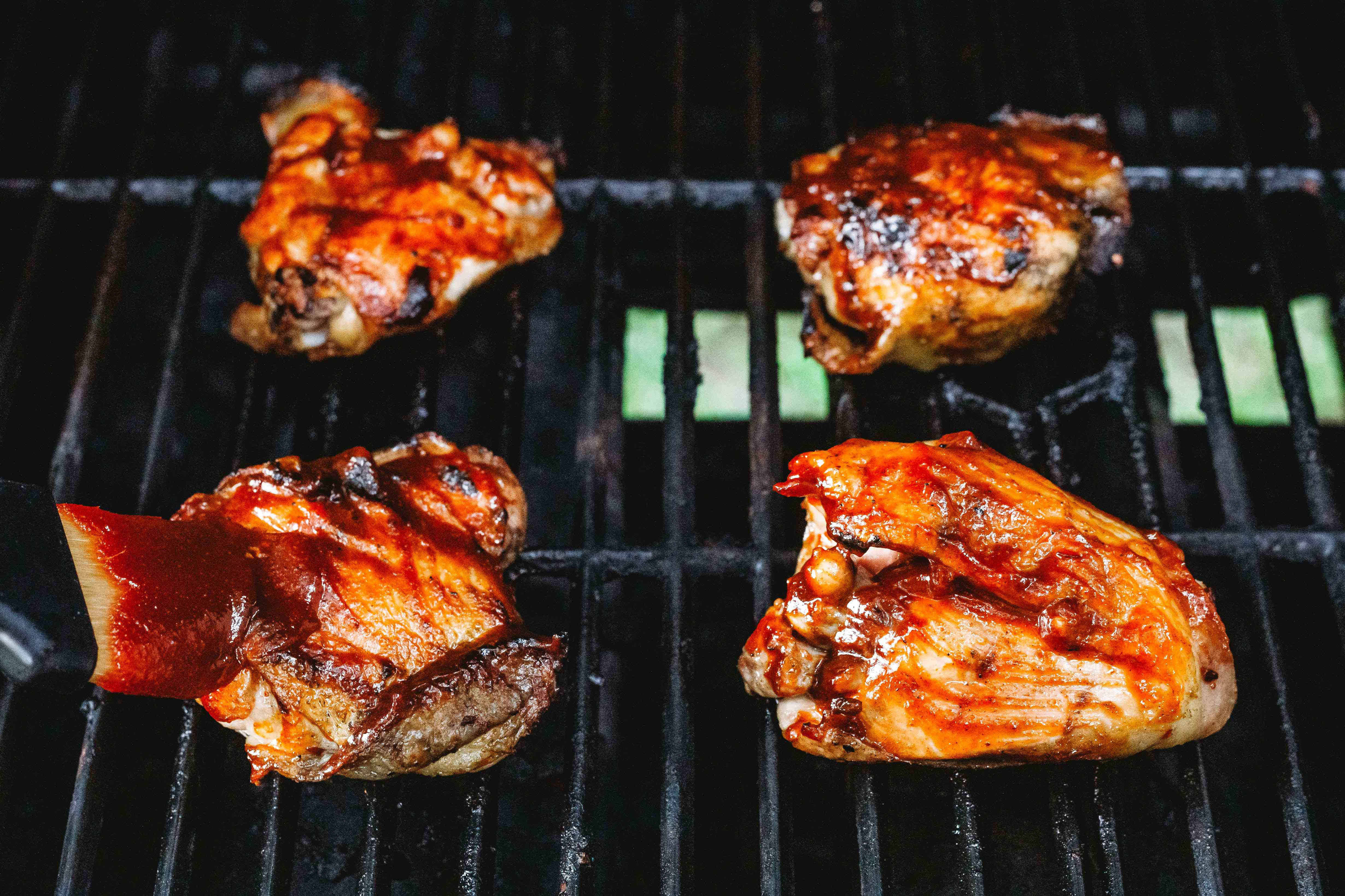 chicken on the grill brushed with bbq sauce