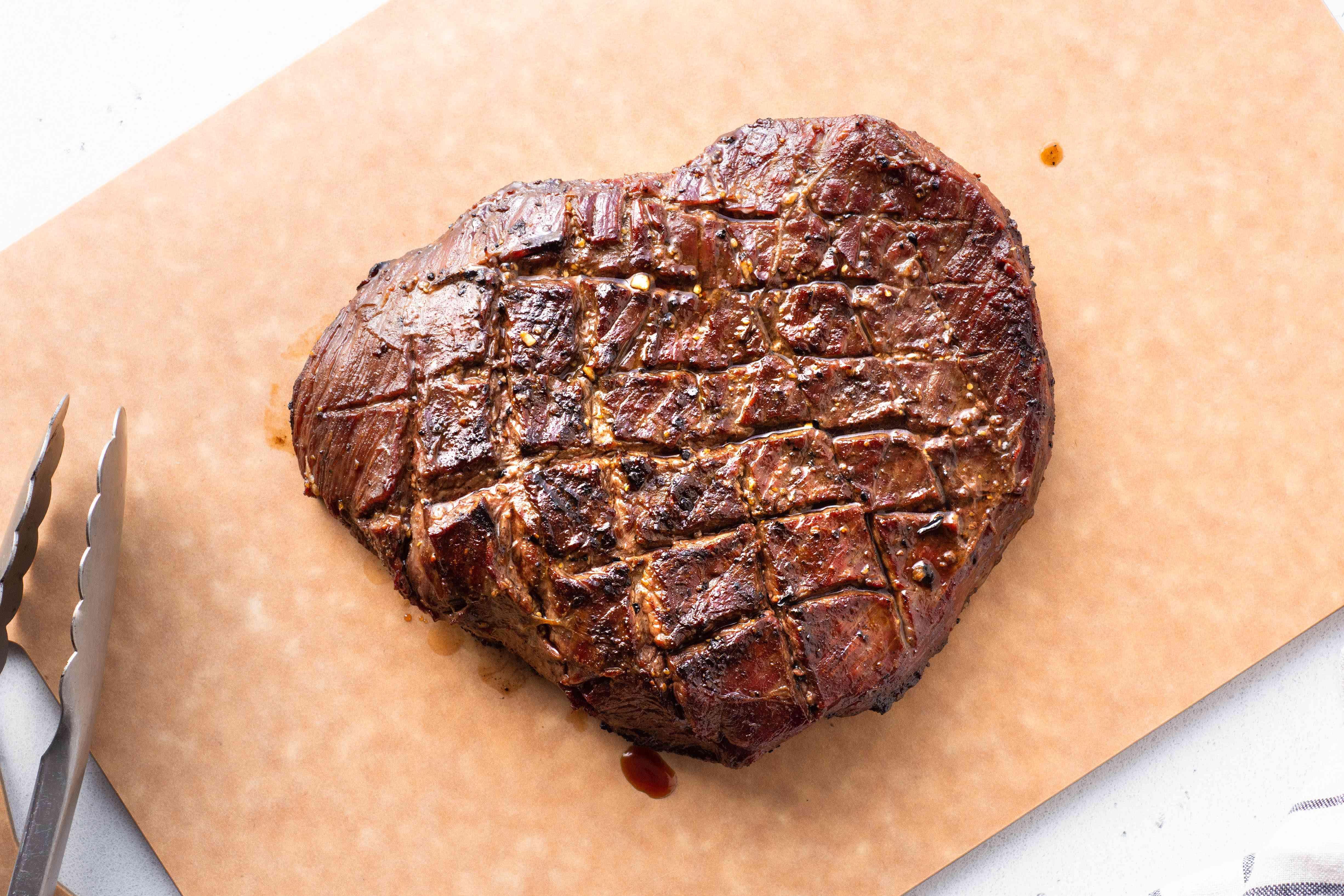 grilled flank steak resting on a cutting board