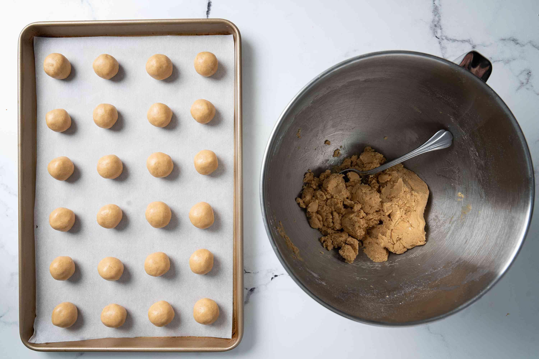 Peanut butter dough rolled into balls on a baking sheet