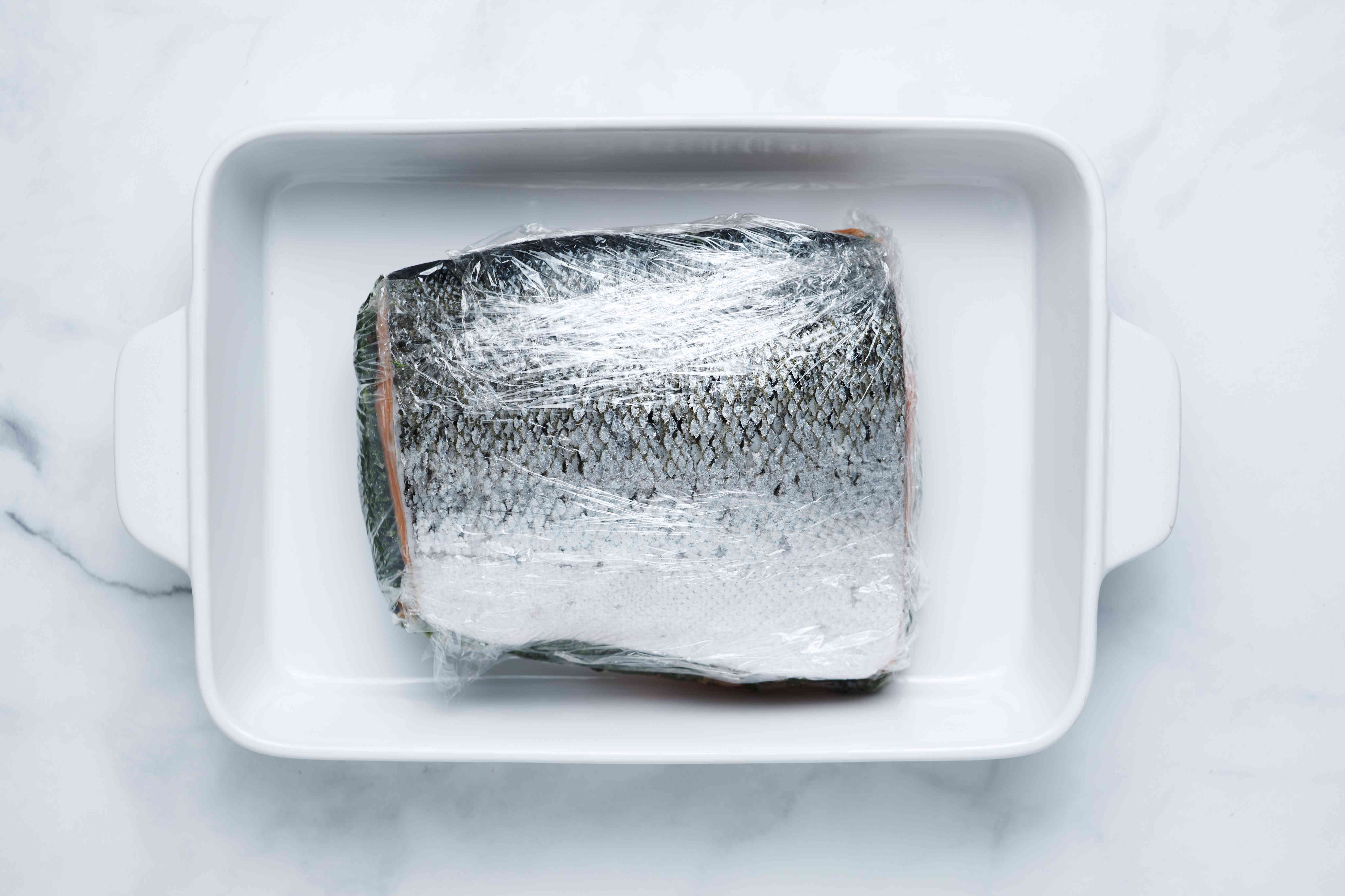 salmon fillets wrapped in plastic in a baking dish
