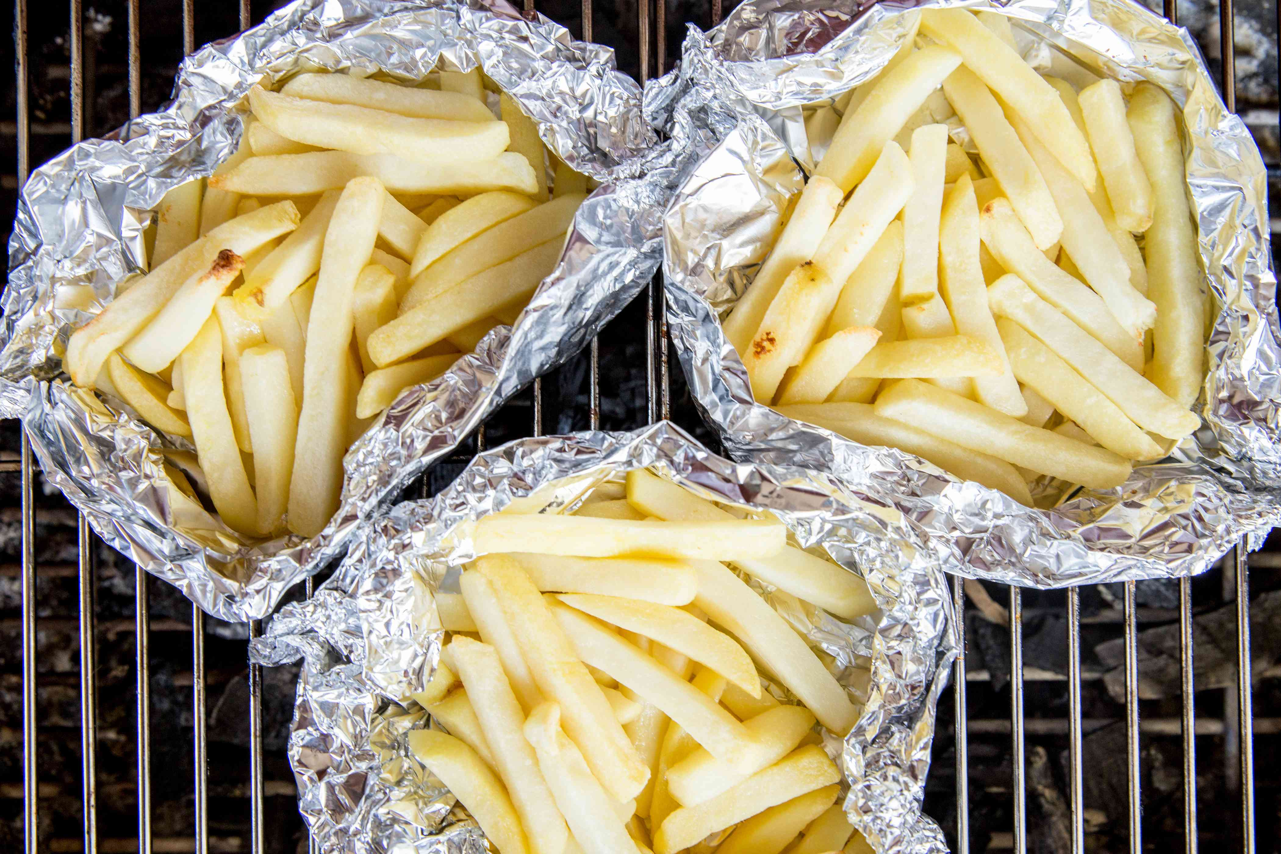 french fries in aluminum foil boats on a grill