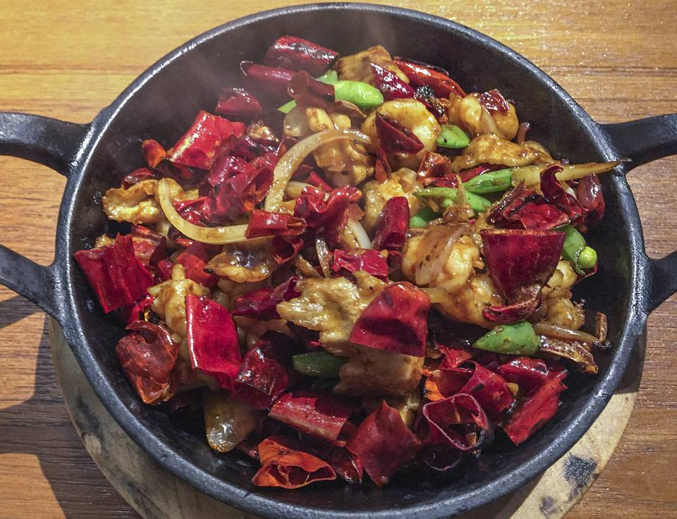 Chinese Sichuan Cuisine, Seafood and Pork with Hot and Spicy Chilli Peppers in Iron Pot