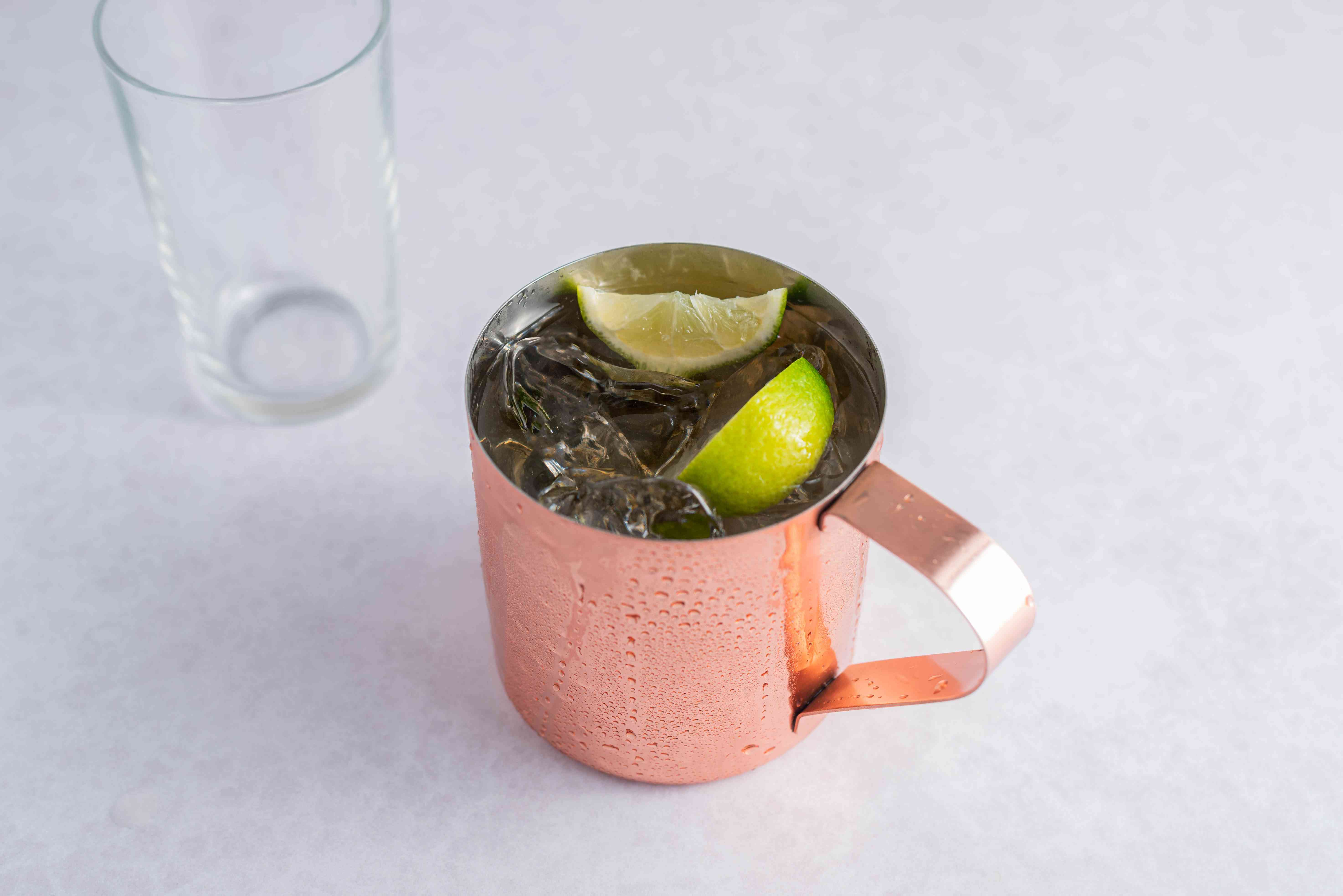 Top with ginger beer and garnish with lime wedges