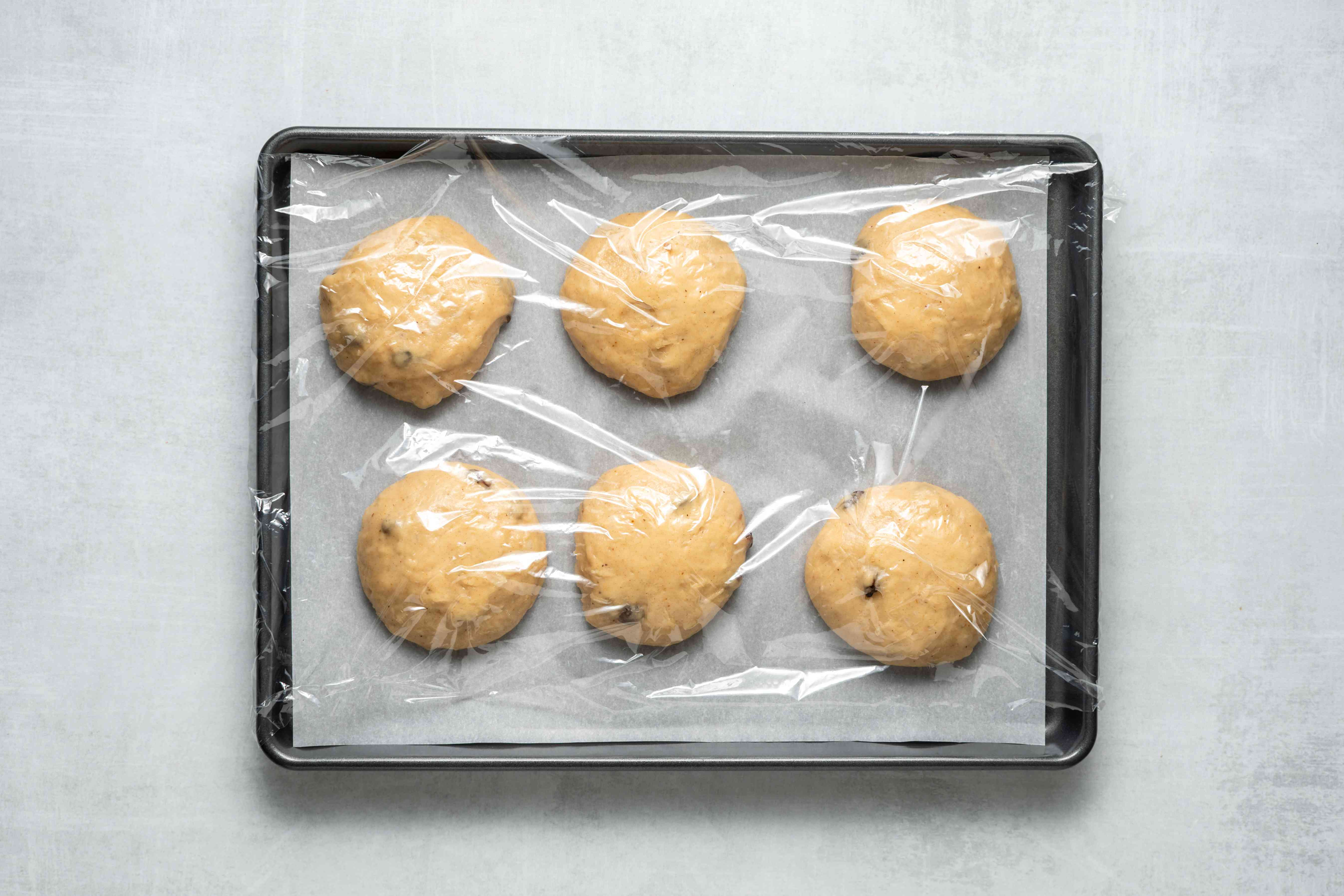 raisin buns rising on a baking sheet covered with plastic wrap