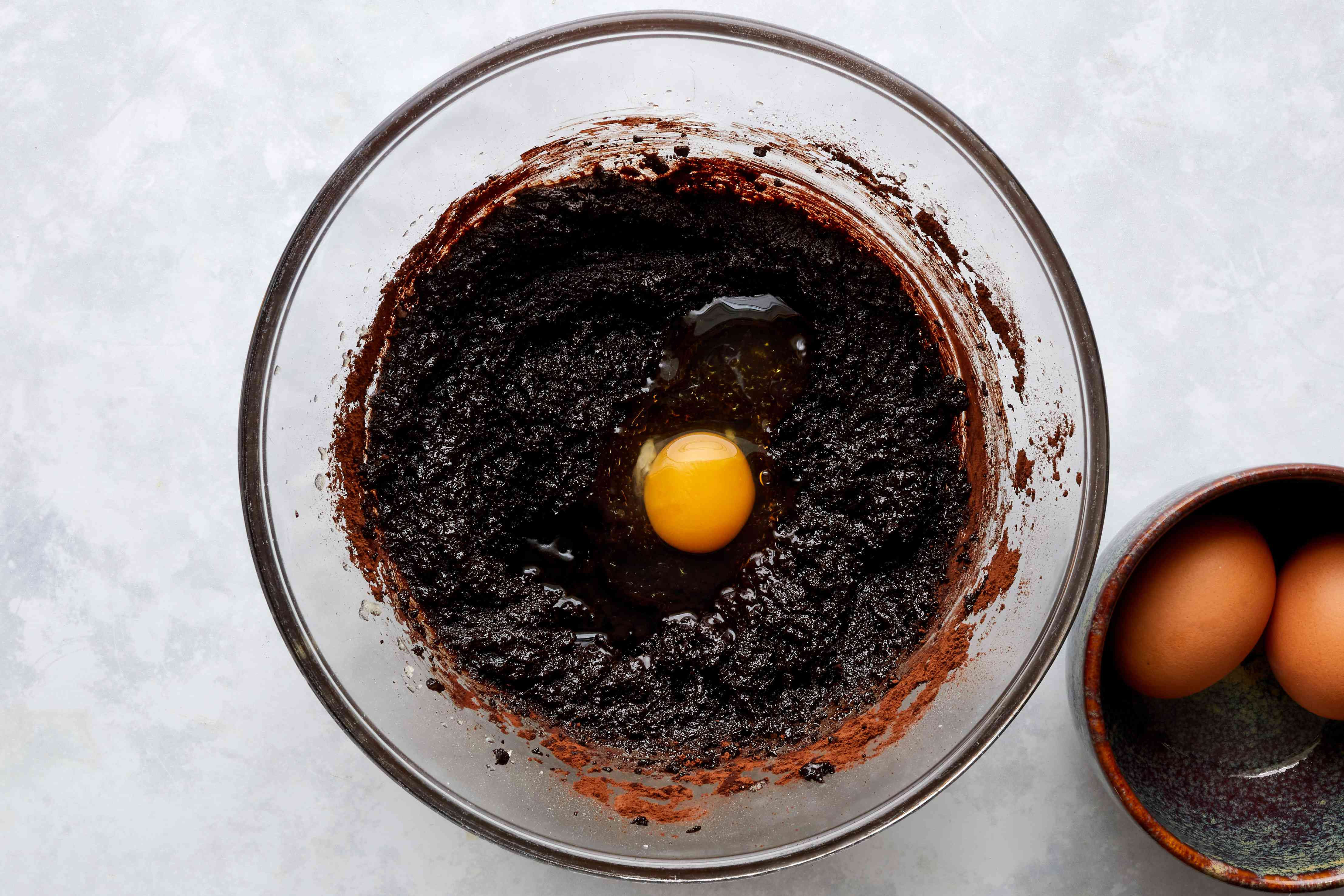 egg on top of the chocolate batter in a large glass dough