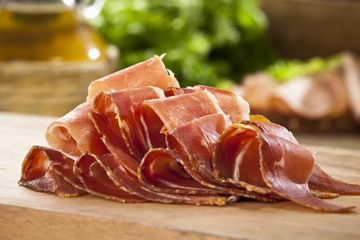 Sliced prosciutto on a wood block