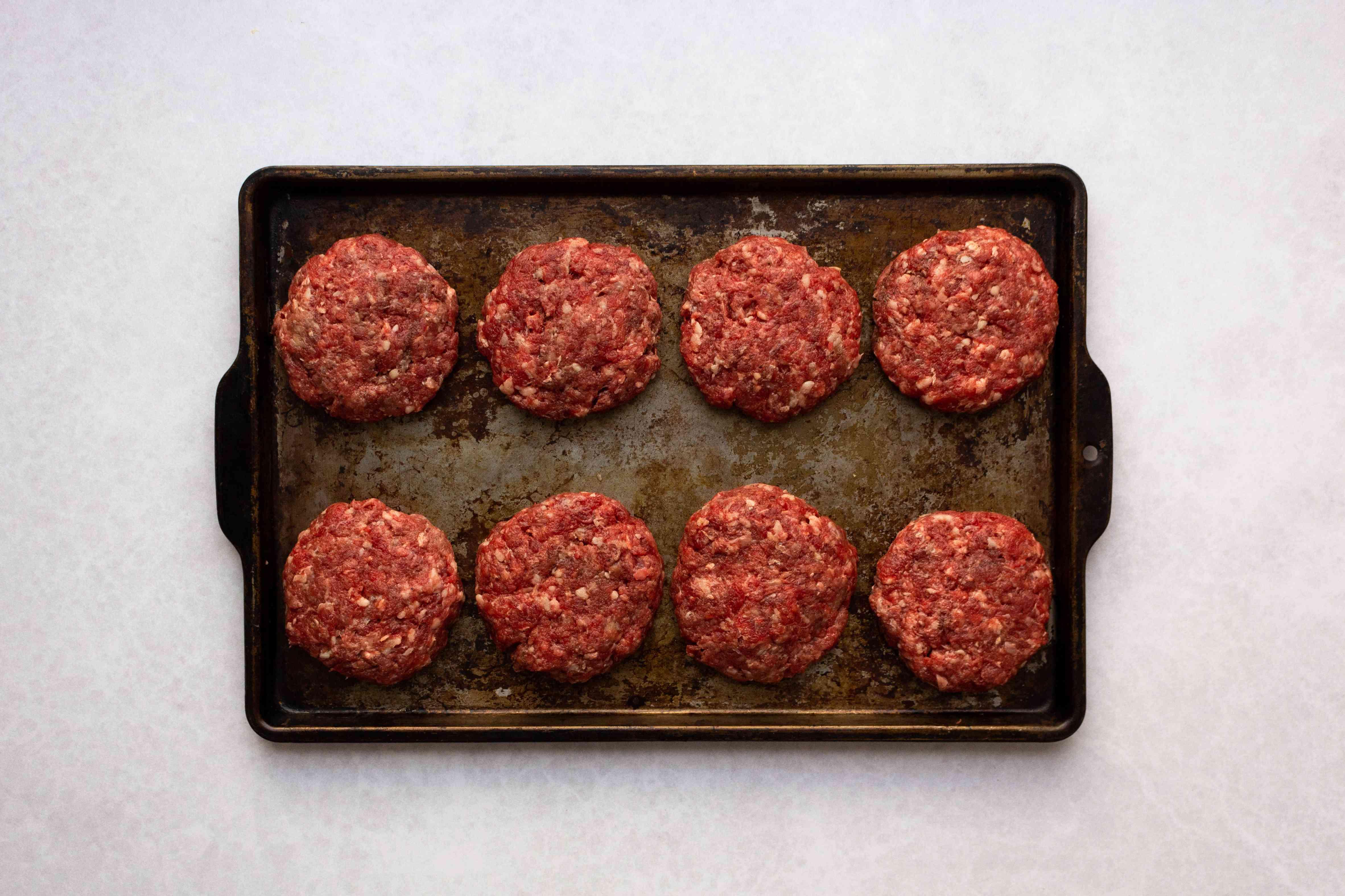 shaped hamburger patties on baking sheet