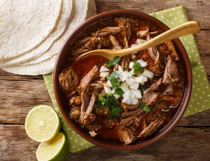 Birria with tortillas and lime wedges
