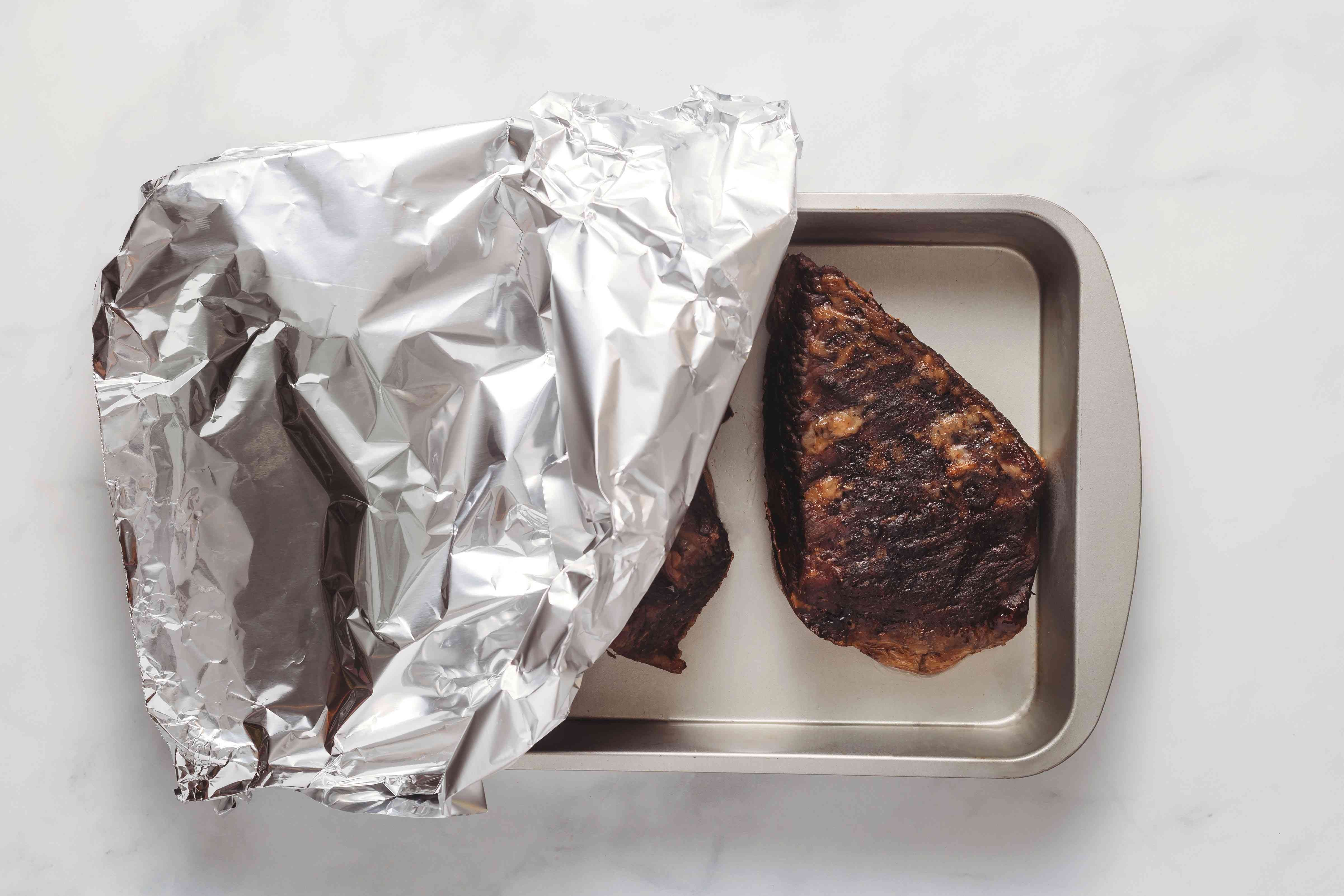 beef brisket in a baking dish covered with aluminum foil