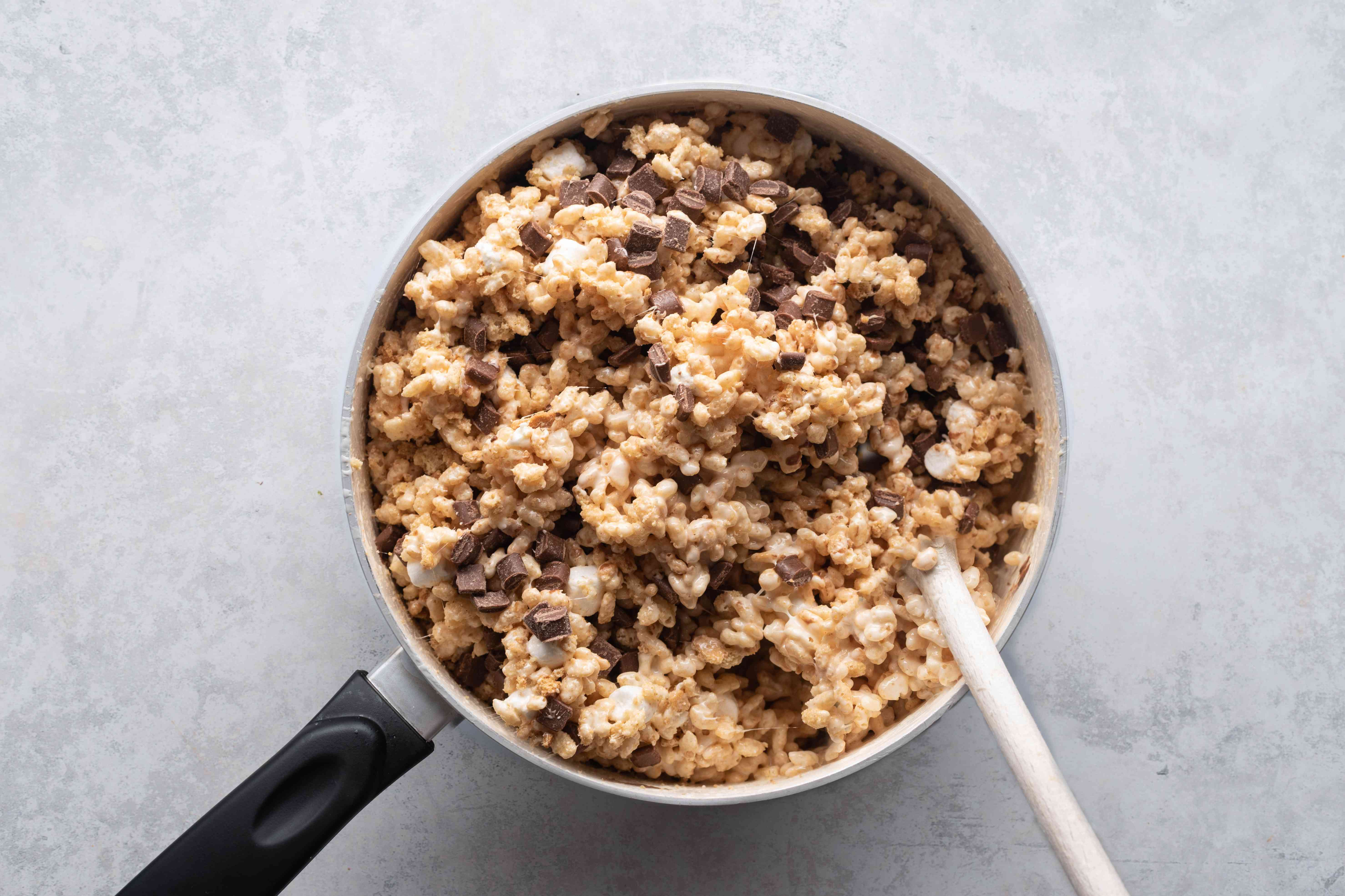 rice krispie mixture with chocolate pieces in a pan