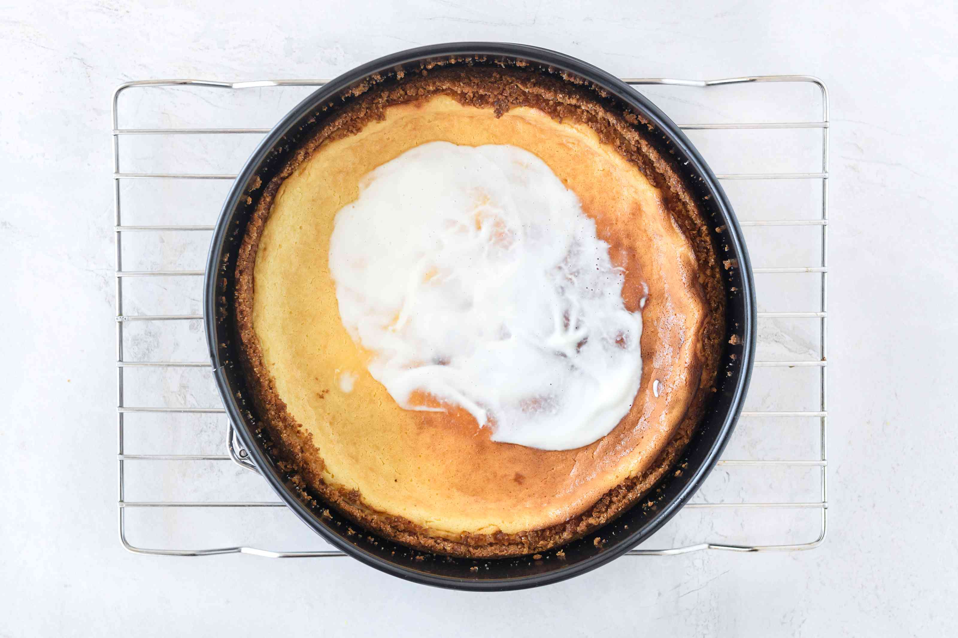 Dairy-free cheesecake topped with dairy-free sour cream on wire cooling rack