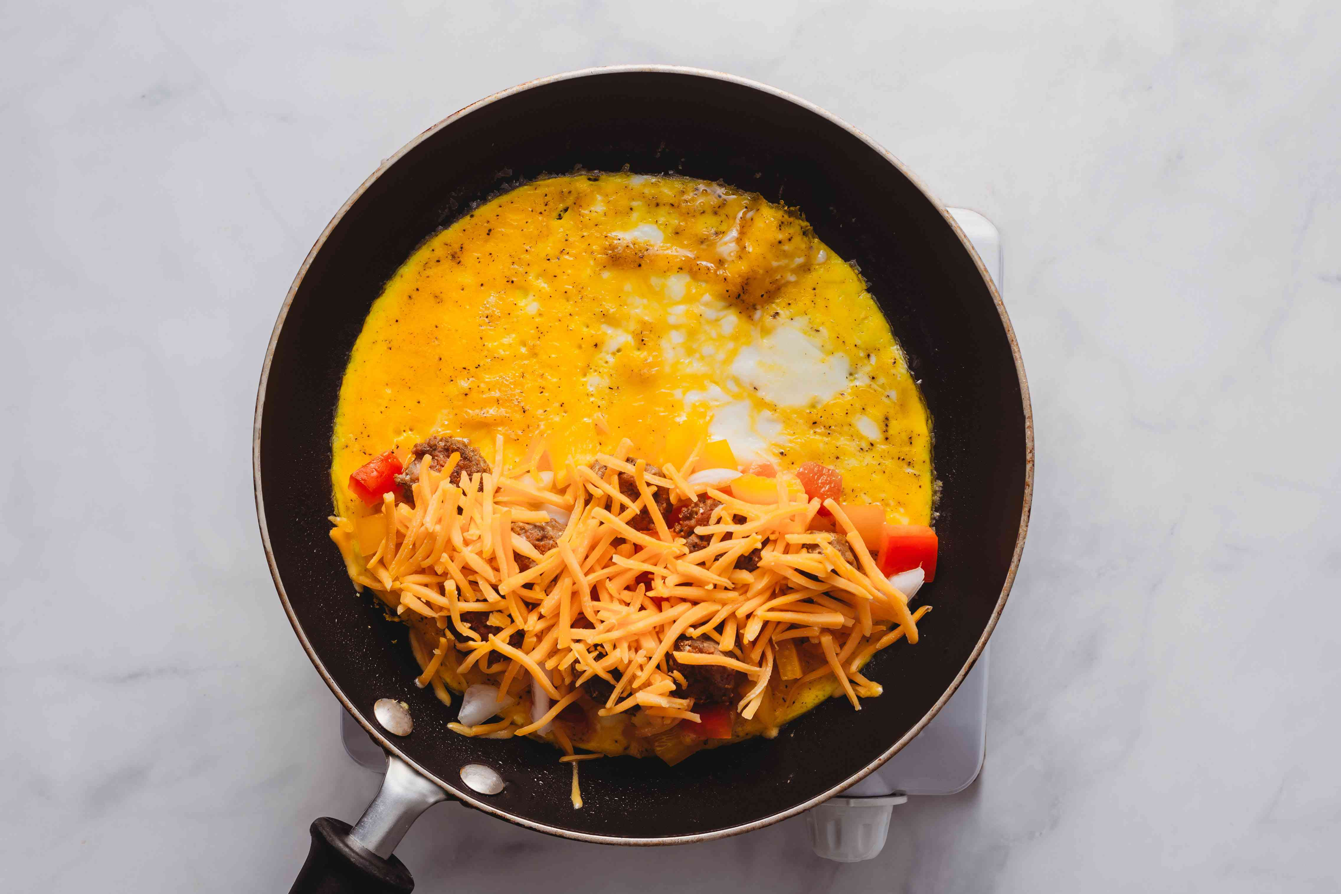 cheese on top of the omelet in the skillet