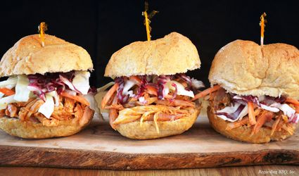 Three barbecued pulled chicken sandwiches on a cutting board