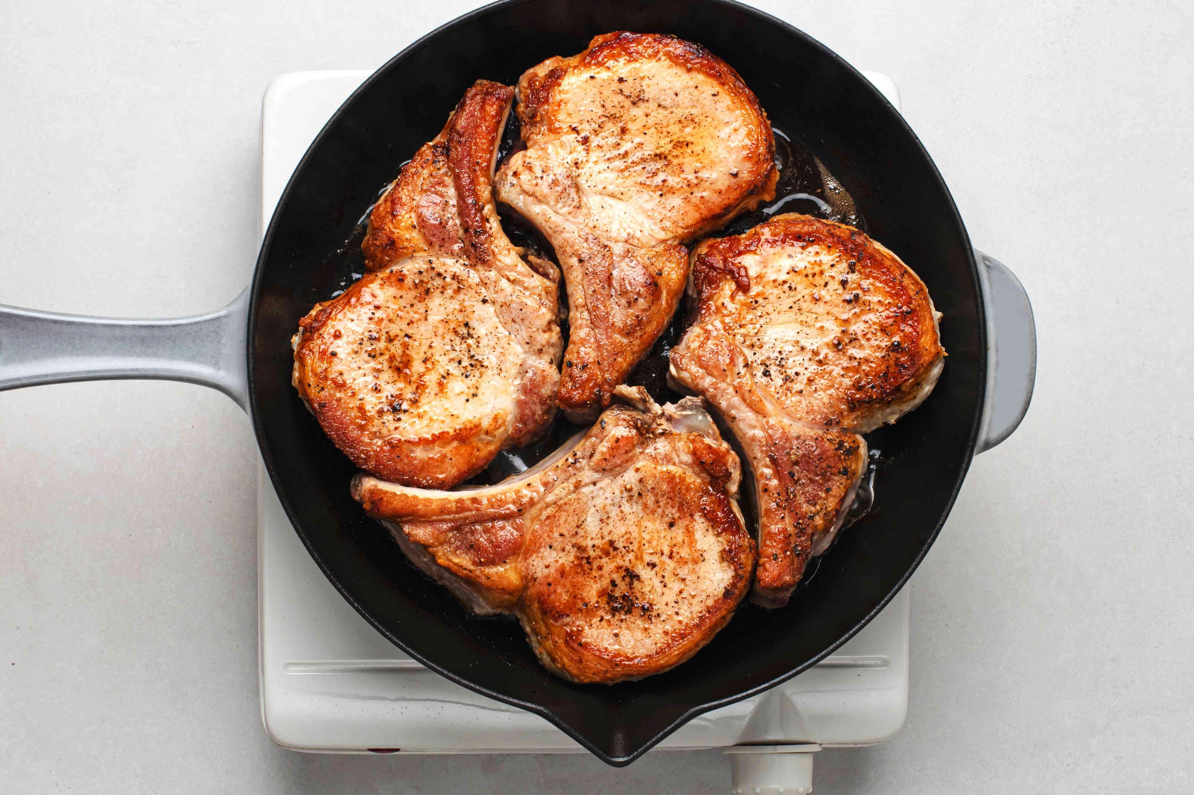 pork chops cooking in a skillet