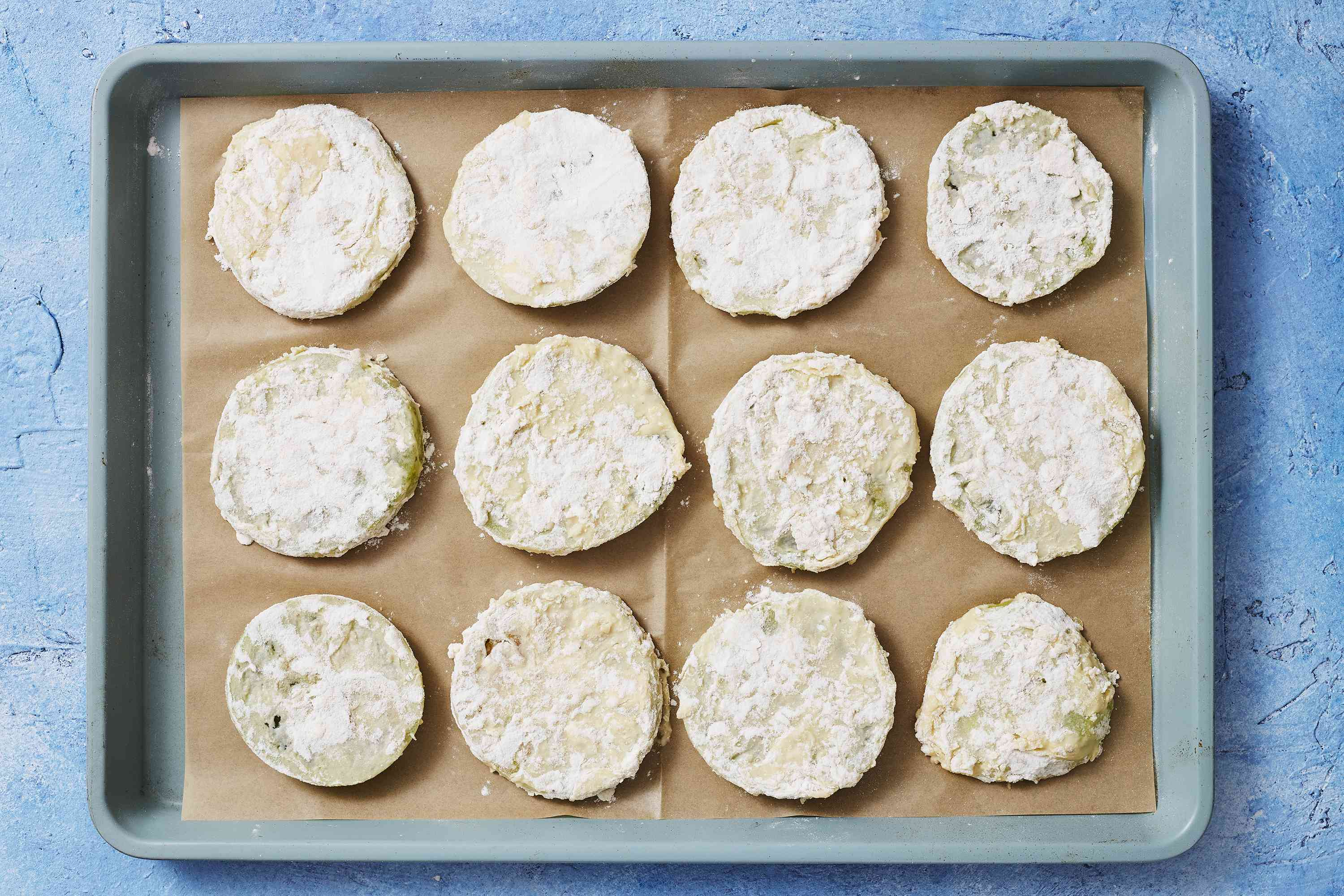 Battered green tomato slices on a parchment-lined baking sheet