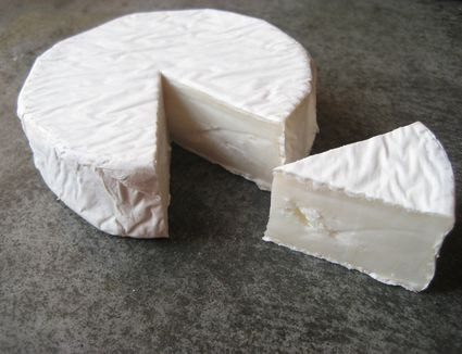 A wheel of goat brie with a cut out wedge