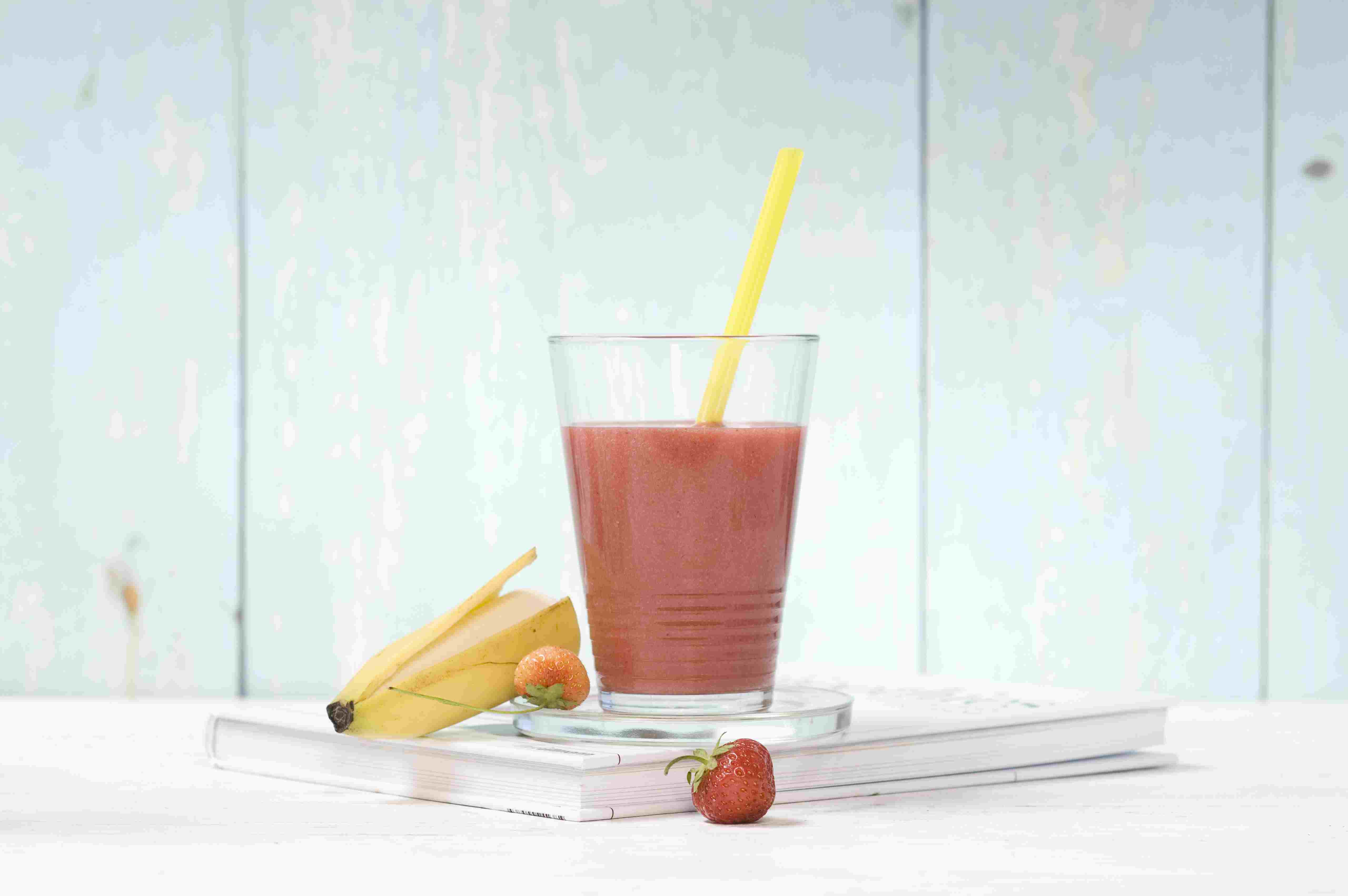 Strawberry banana smoothie in glass with drinking straw