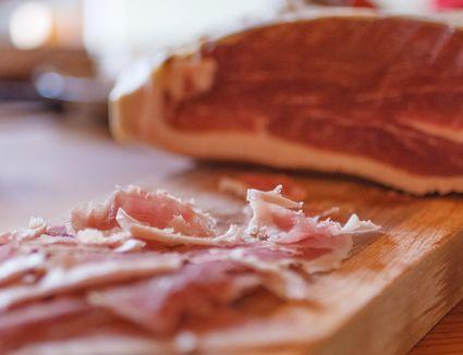 Cured ham on chopping board