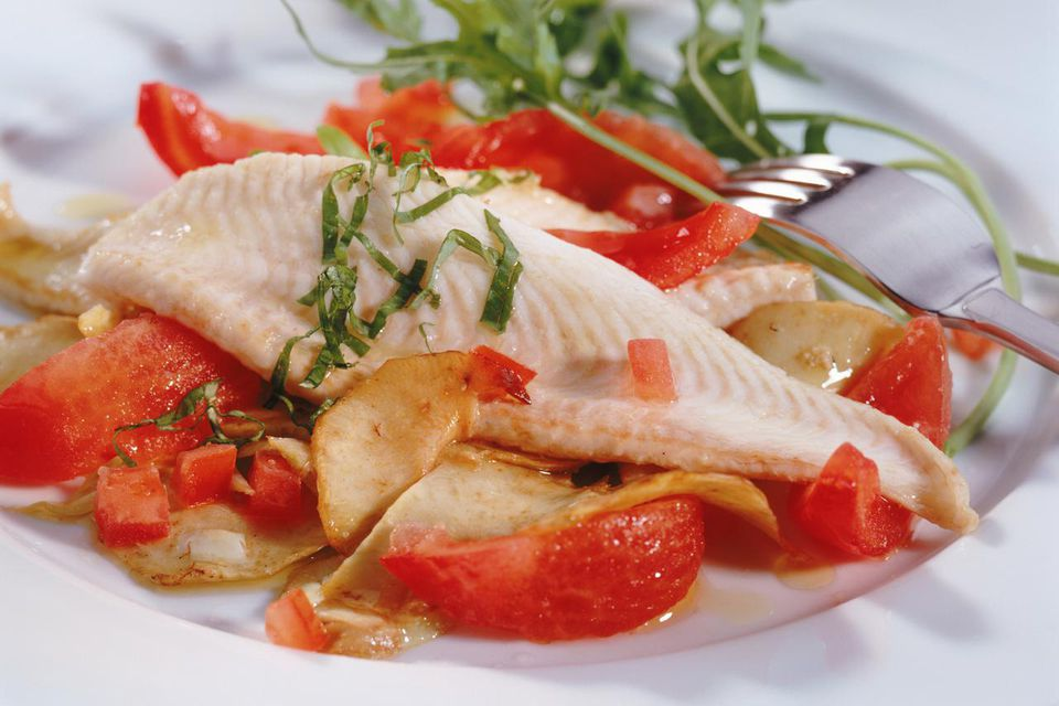 Salad with steamed tomato and fish on plate