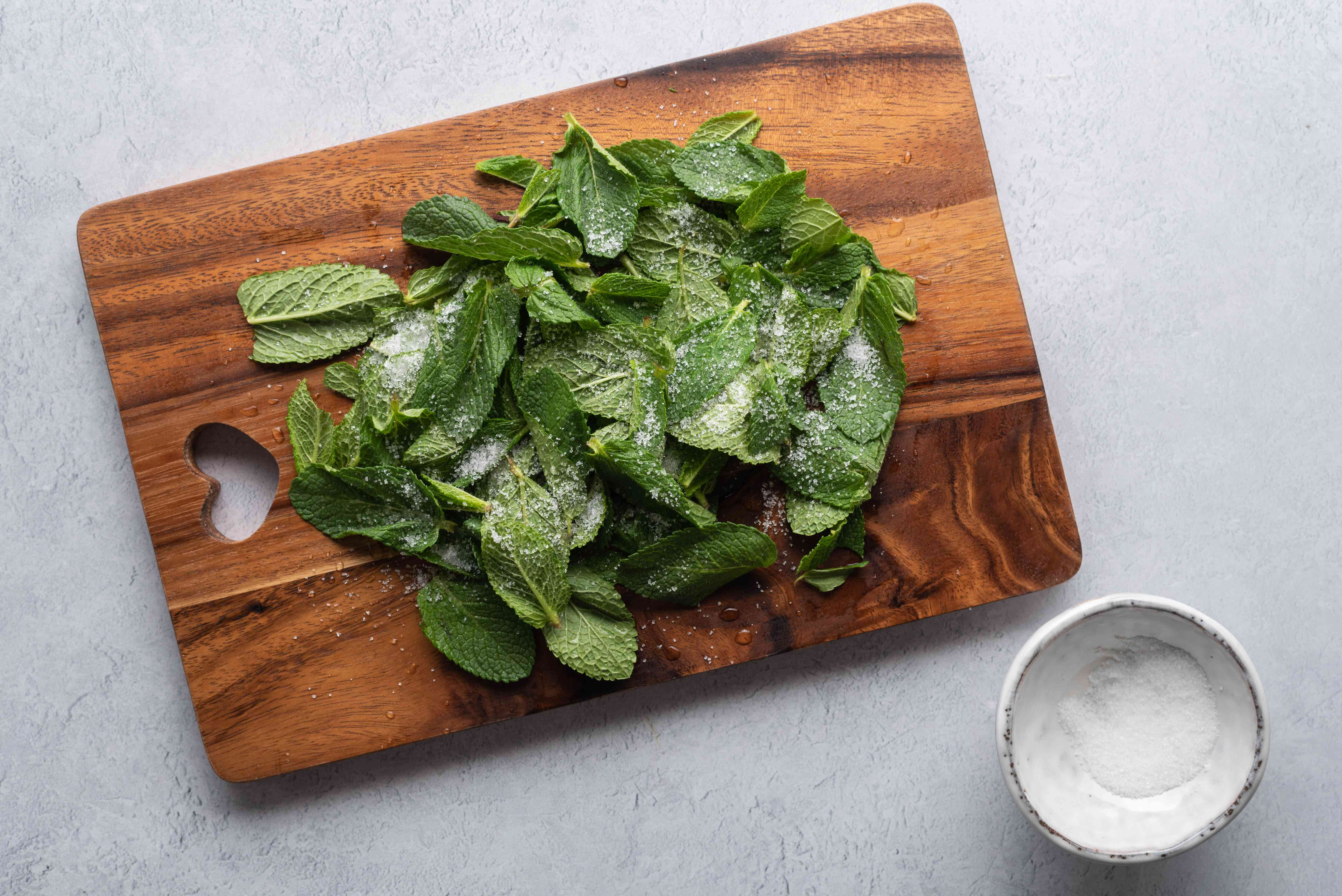 mint leaves sprinkled with sugar, on a wood cutting board