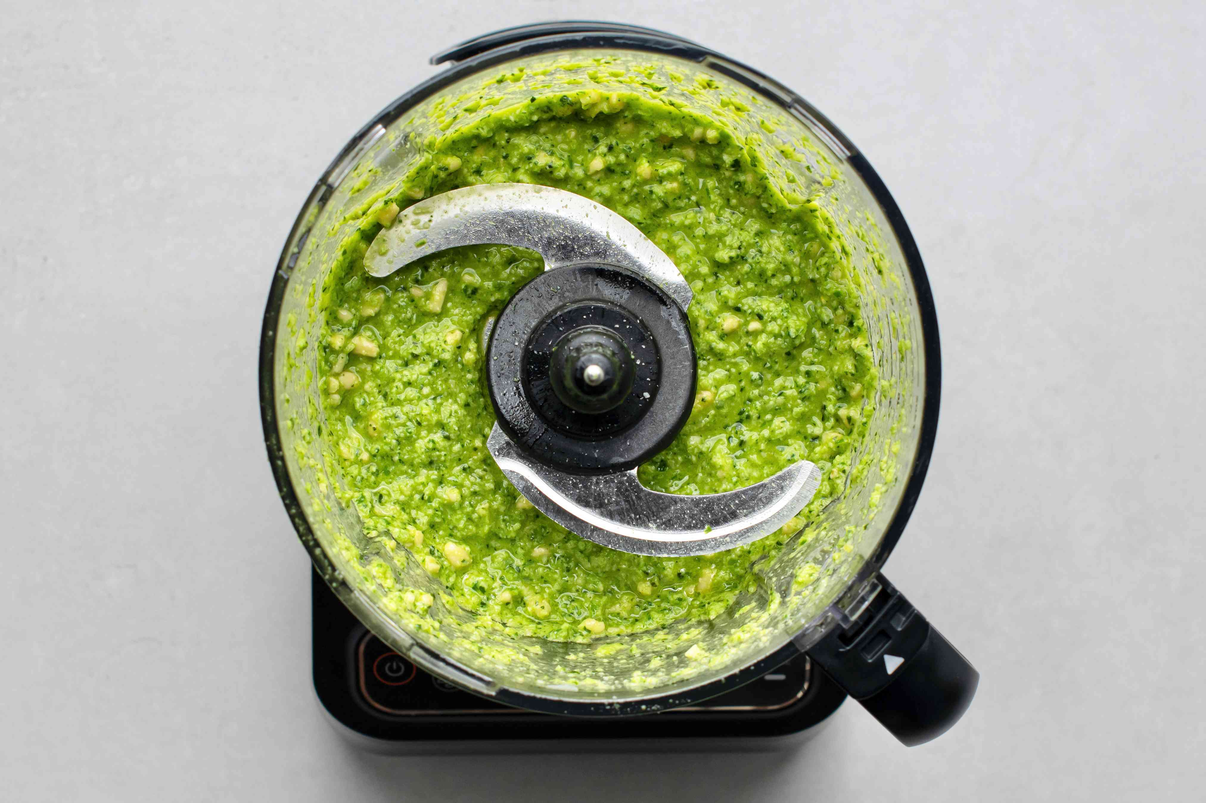 Add pine nuts to the pesto mixture in the food processor