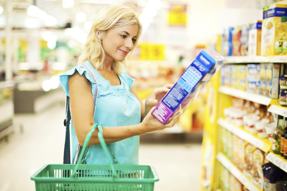 Woman shopping cereals looking at food label