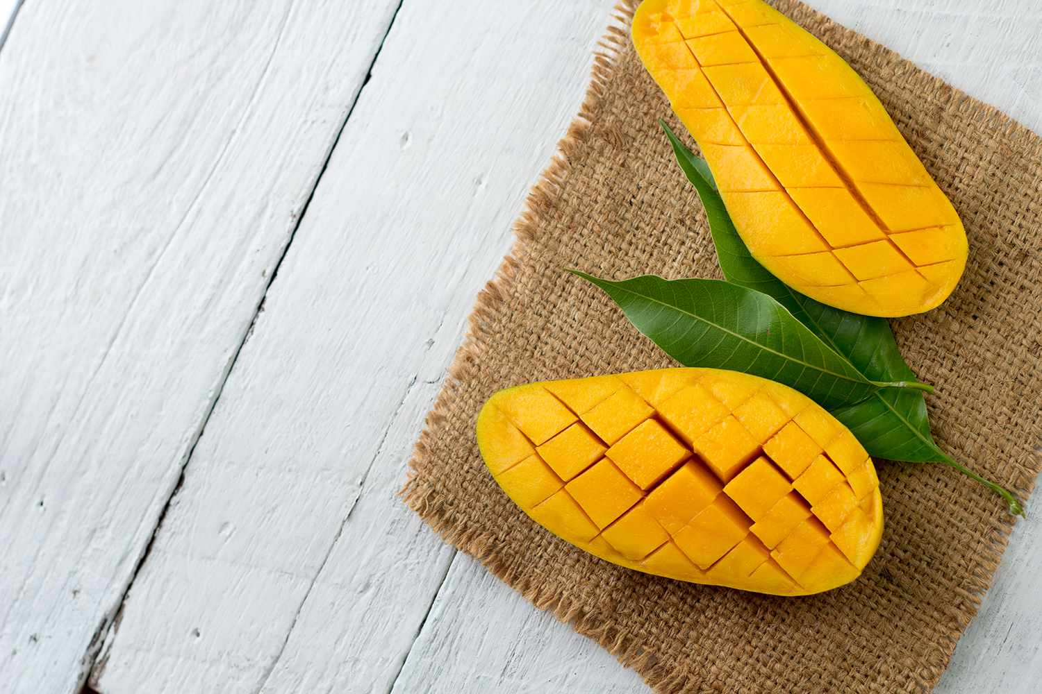 Halved and cubed mango on a piece of burlap